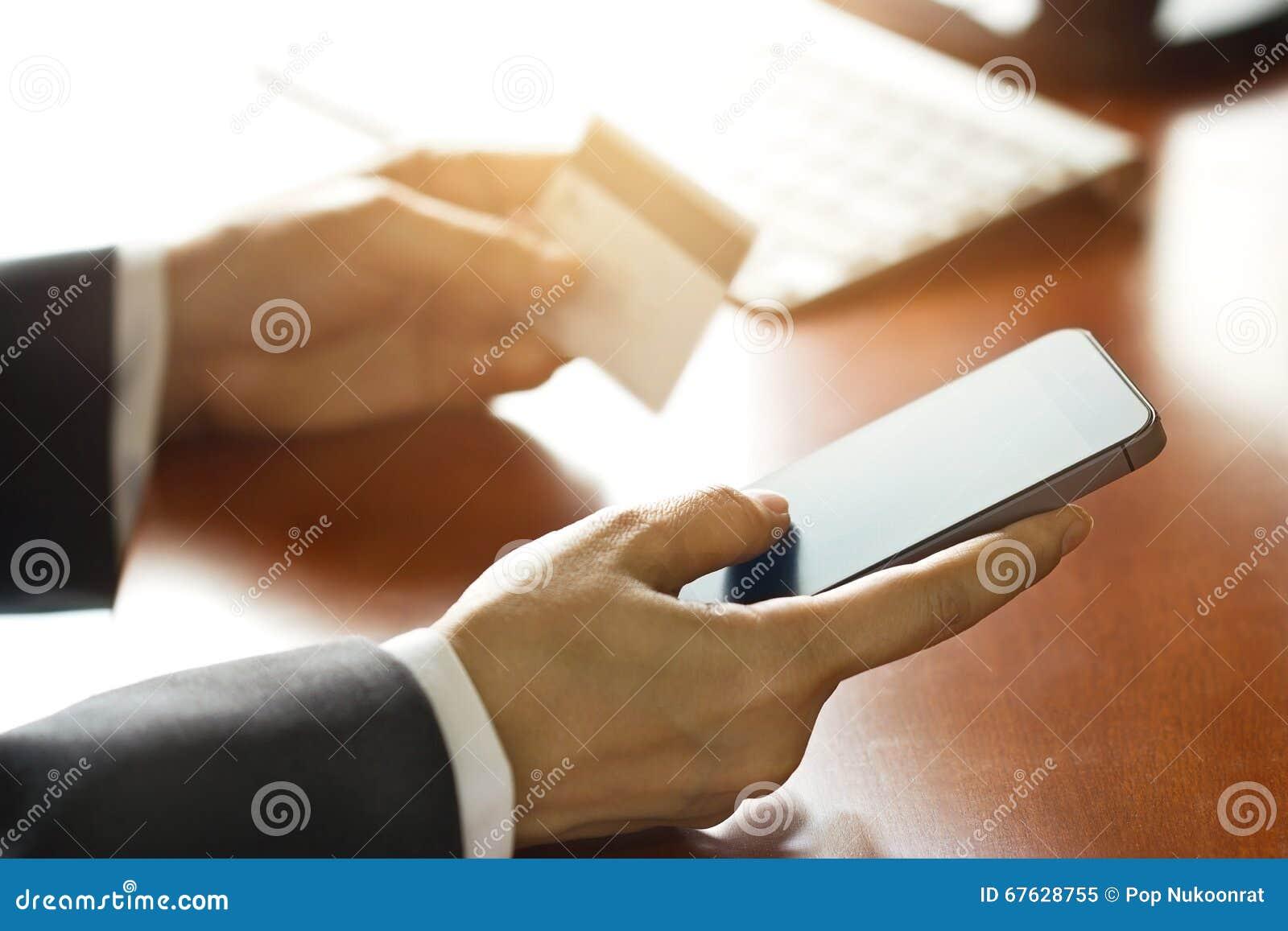 Pagamenti mobili, uomo di affari che usando smartphone e la carta di credito per l acquisto online