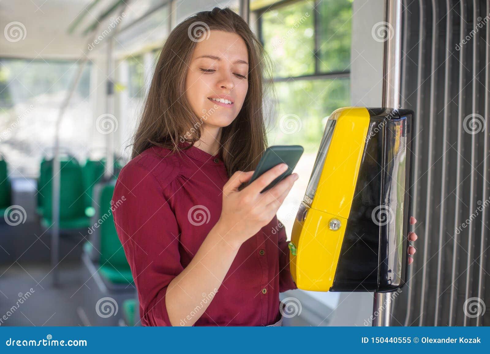 Pagamento femminile della donna conctactless con lo smartphone il trasporto pubblico nel tram