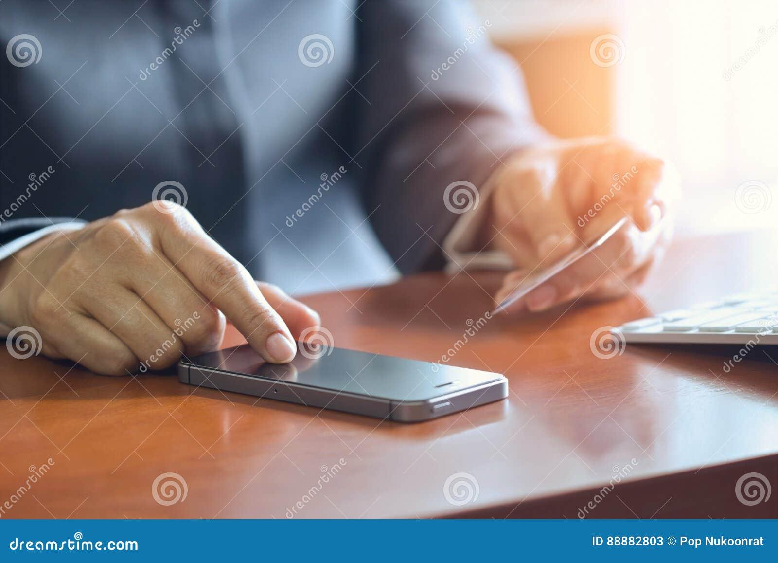 Pagamentos móveis, mãos fêmeas usando o smartphone e o cartão de crédito para a compra em linha