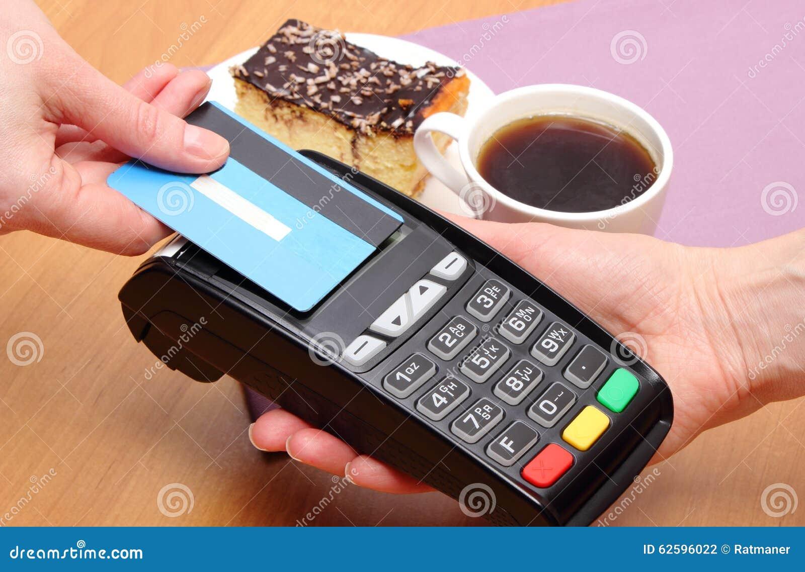 Pagando con la tarjeta de crédito sin contacto el pastel de queso y el café en café, concepto de las finanzas