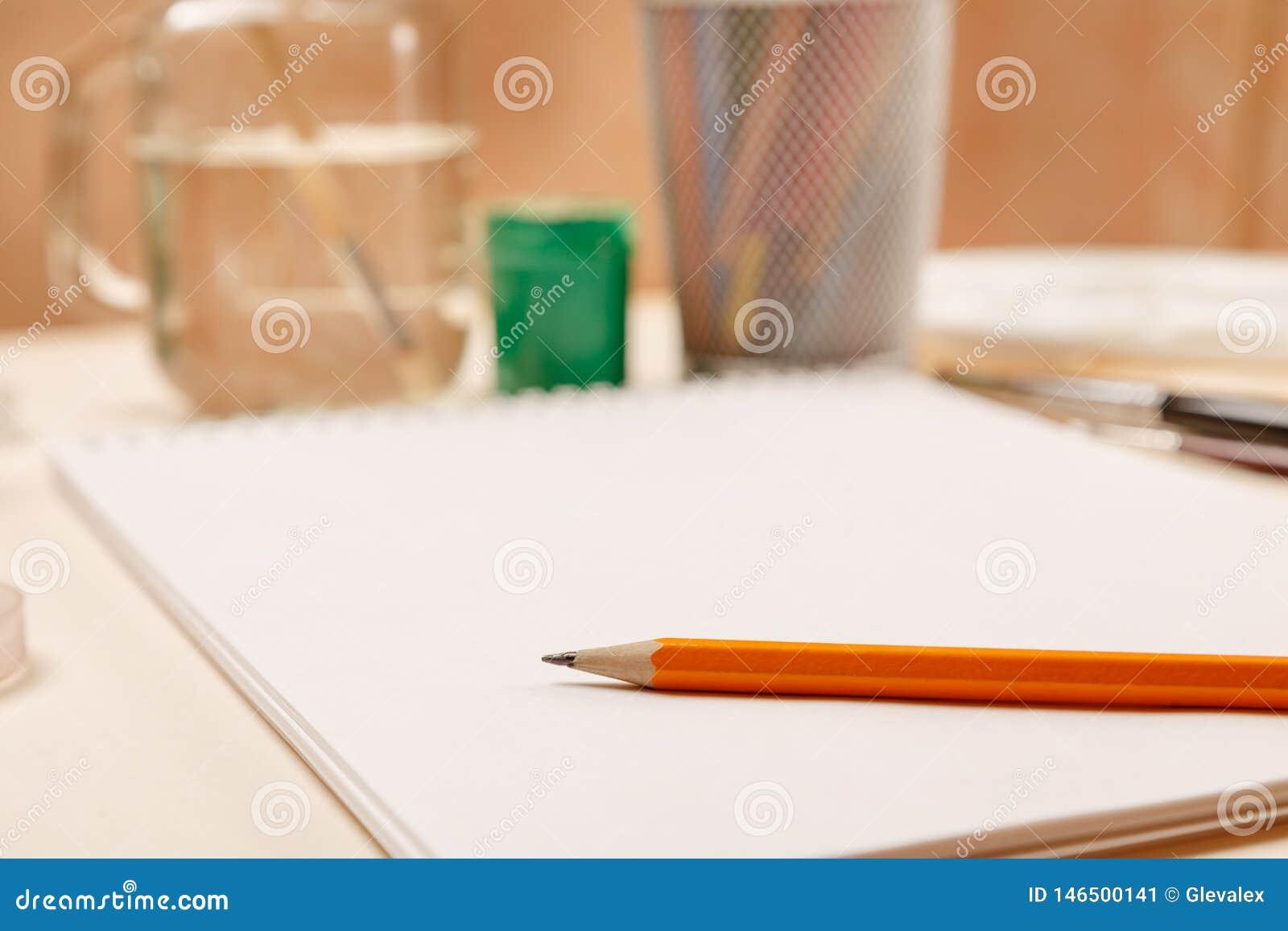 Page de papier blanche avec le crayon là-dessus et toute autre substance pour dessiner, foyer sélectif