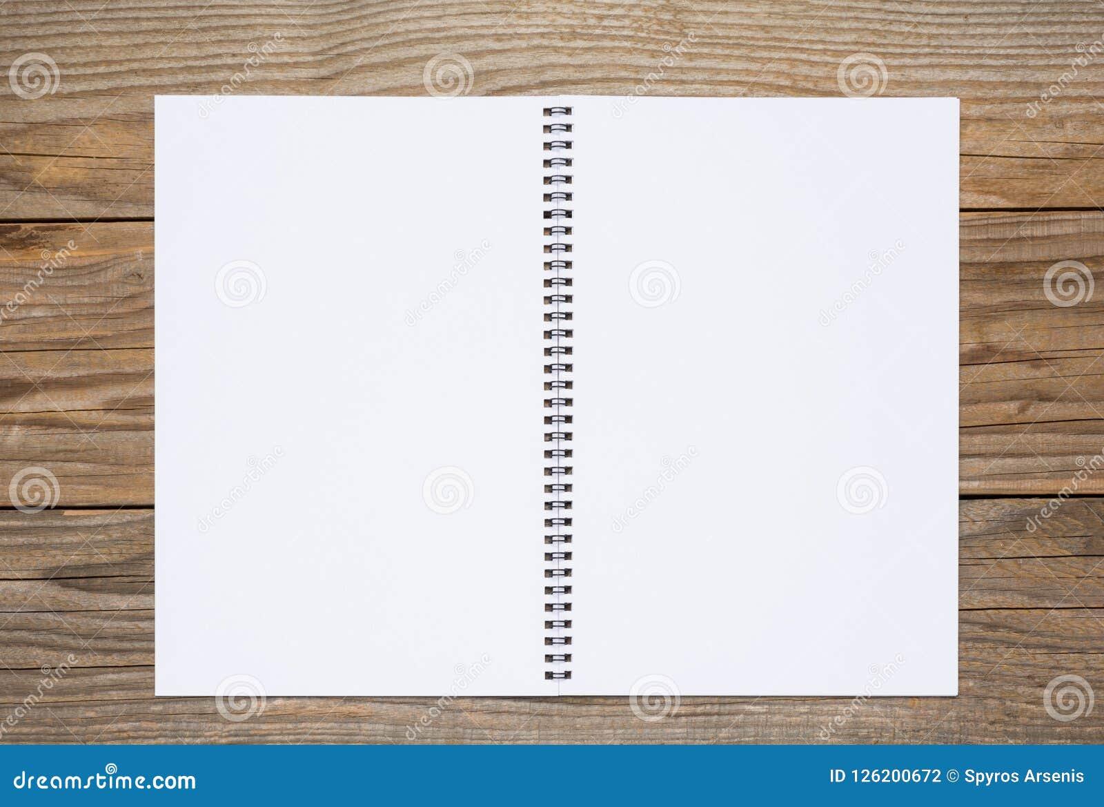 Pagina in bianco di uno sketchbook su una vecchia tavola di legno