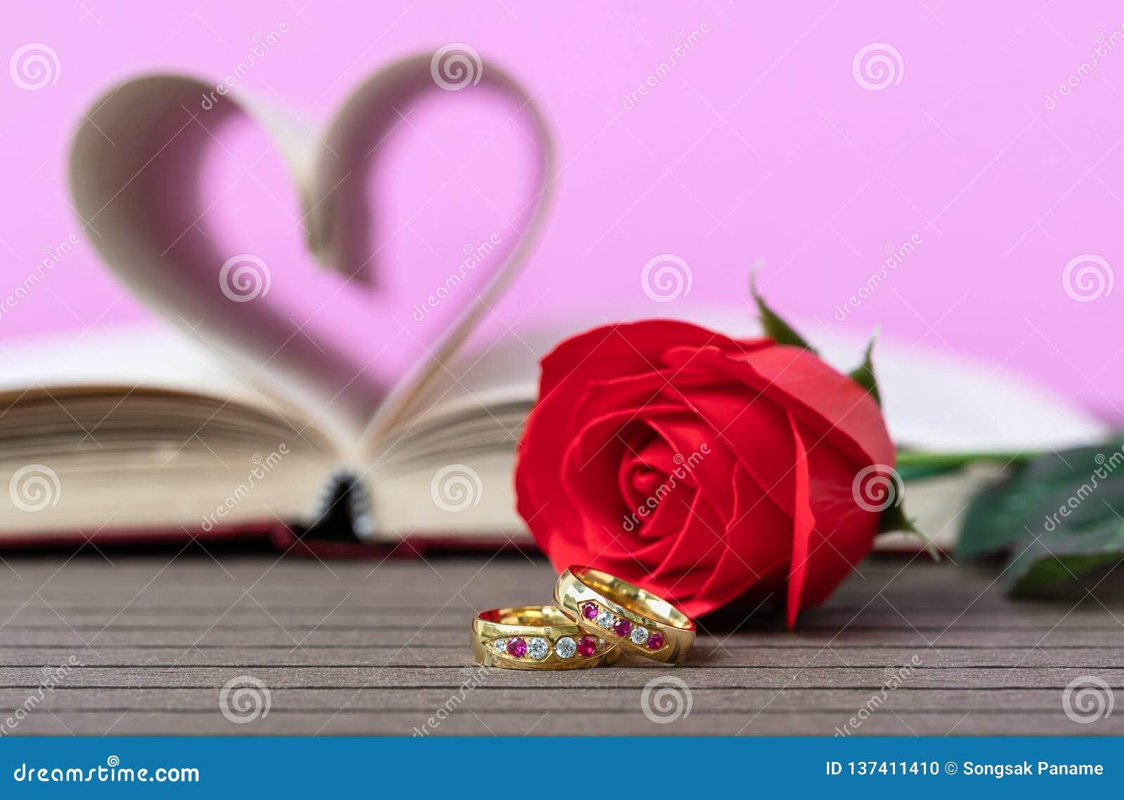 Pagina s van boek gebogen hartvorm met trouwring