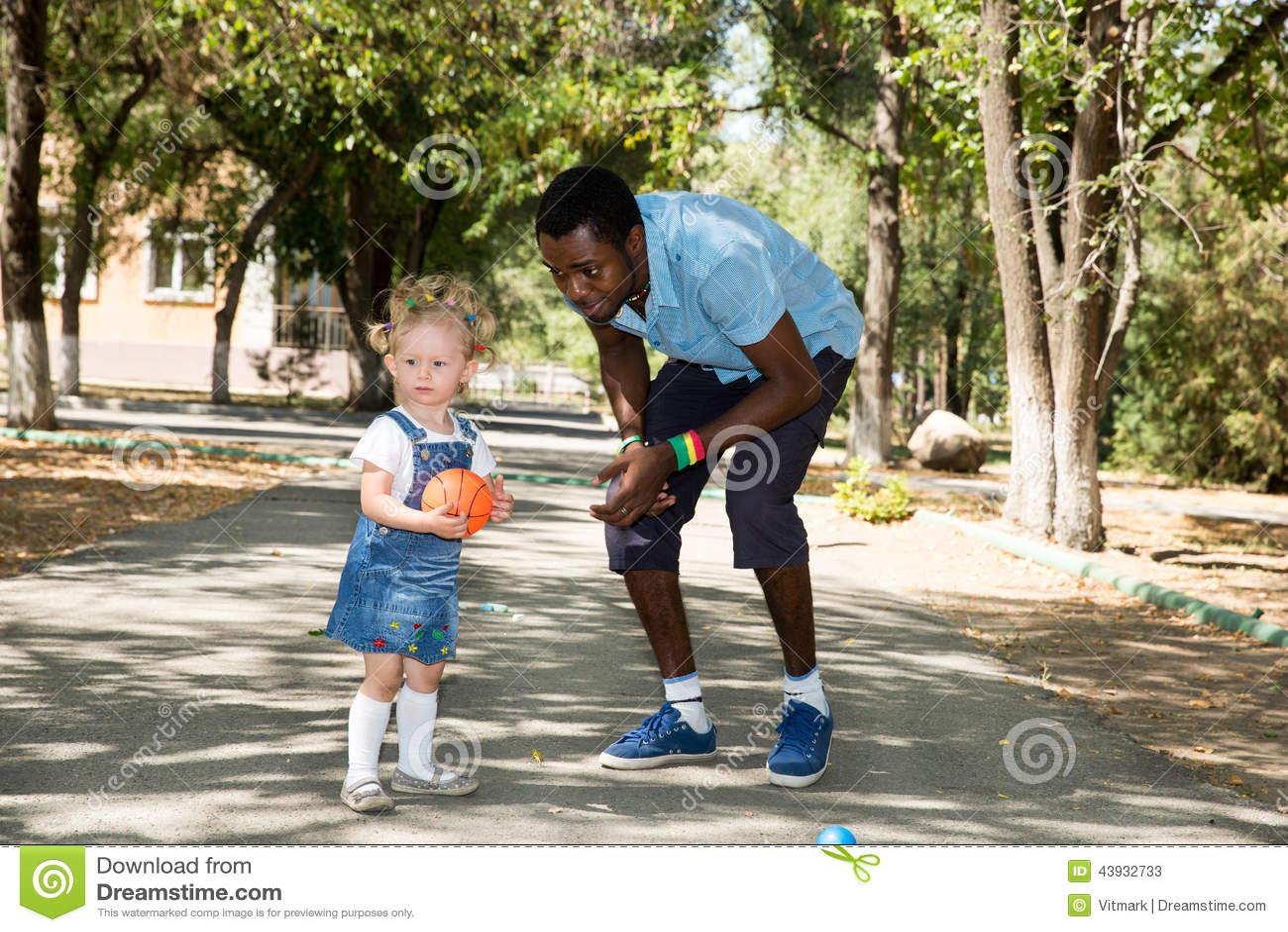 Pai afro-americano novo do deus com a menina que joga o futebol na natureza no verão