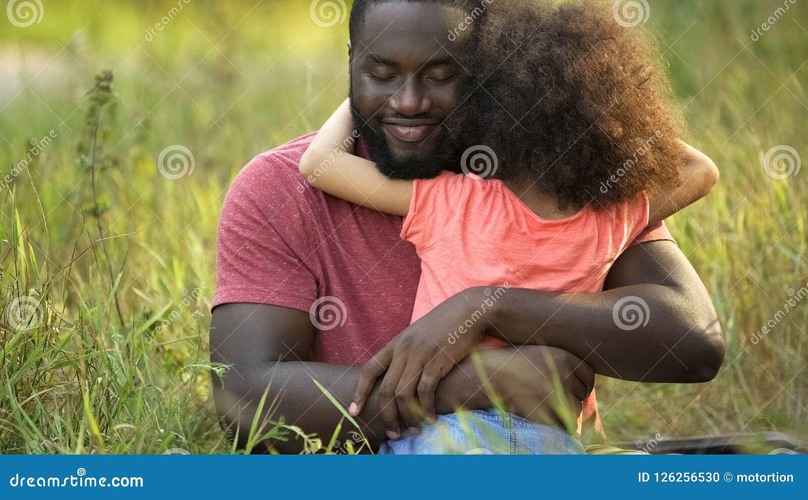 Pai afro-americano que aprecia o passatempo do prazer com sua filha pequena
