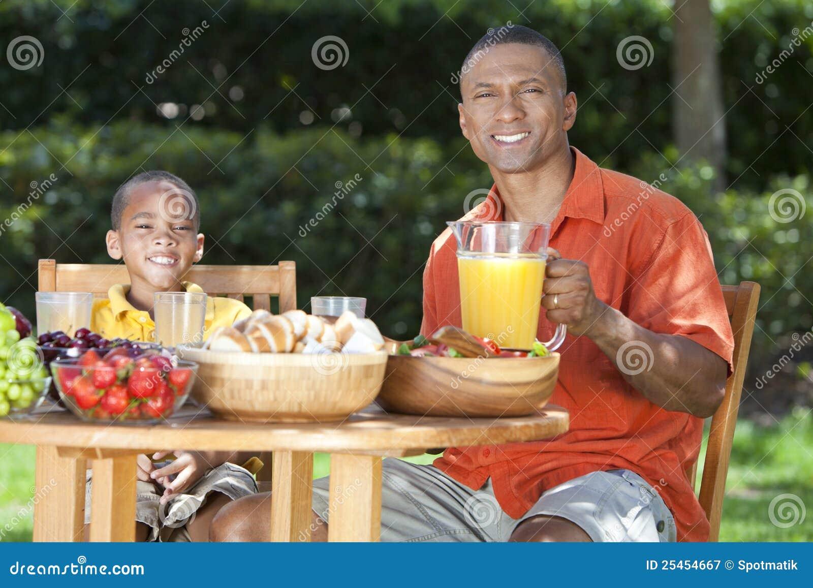 Pai & filho do americano africano que comem o alimento fora