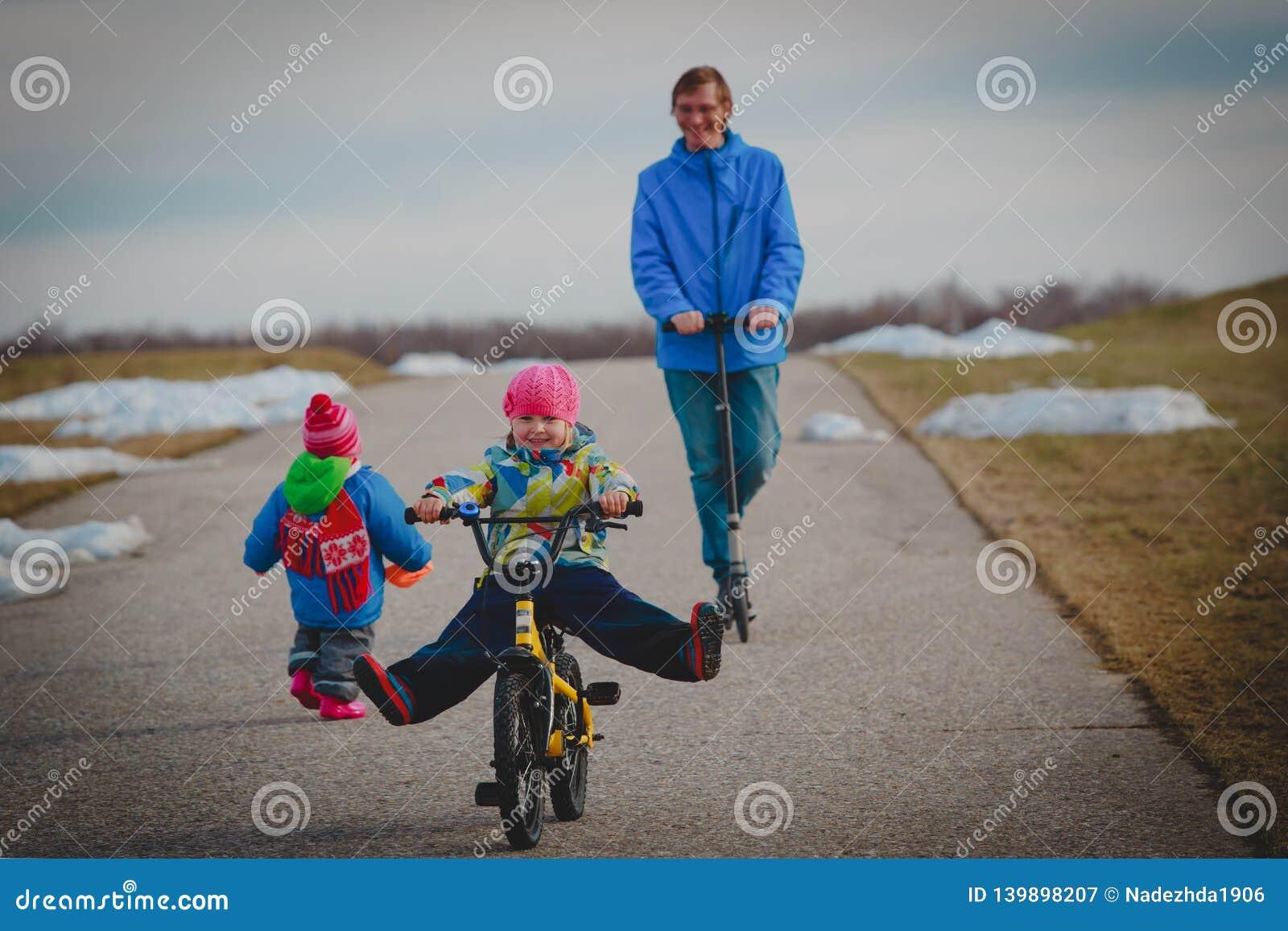 Pai ativo da família do spor no schooter com crianças fora, menina na bicicleta