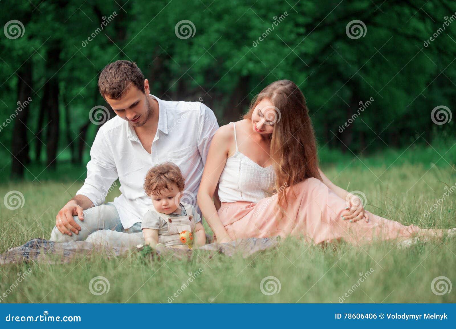 Pai bonito novo, mãe e filho pequeno da criança contra árvores verdes