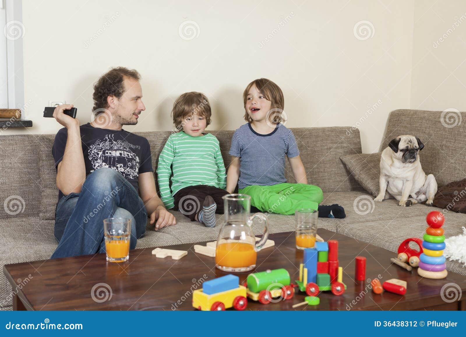 Pai com filhos e cão no sofá