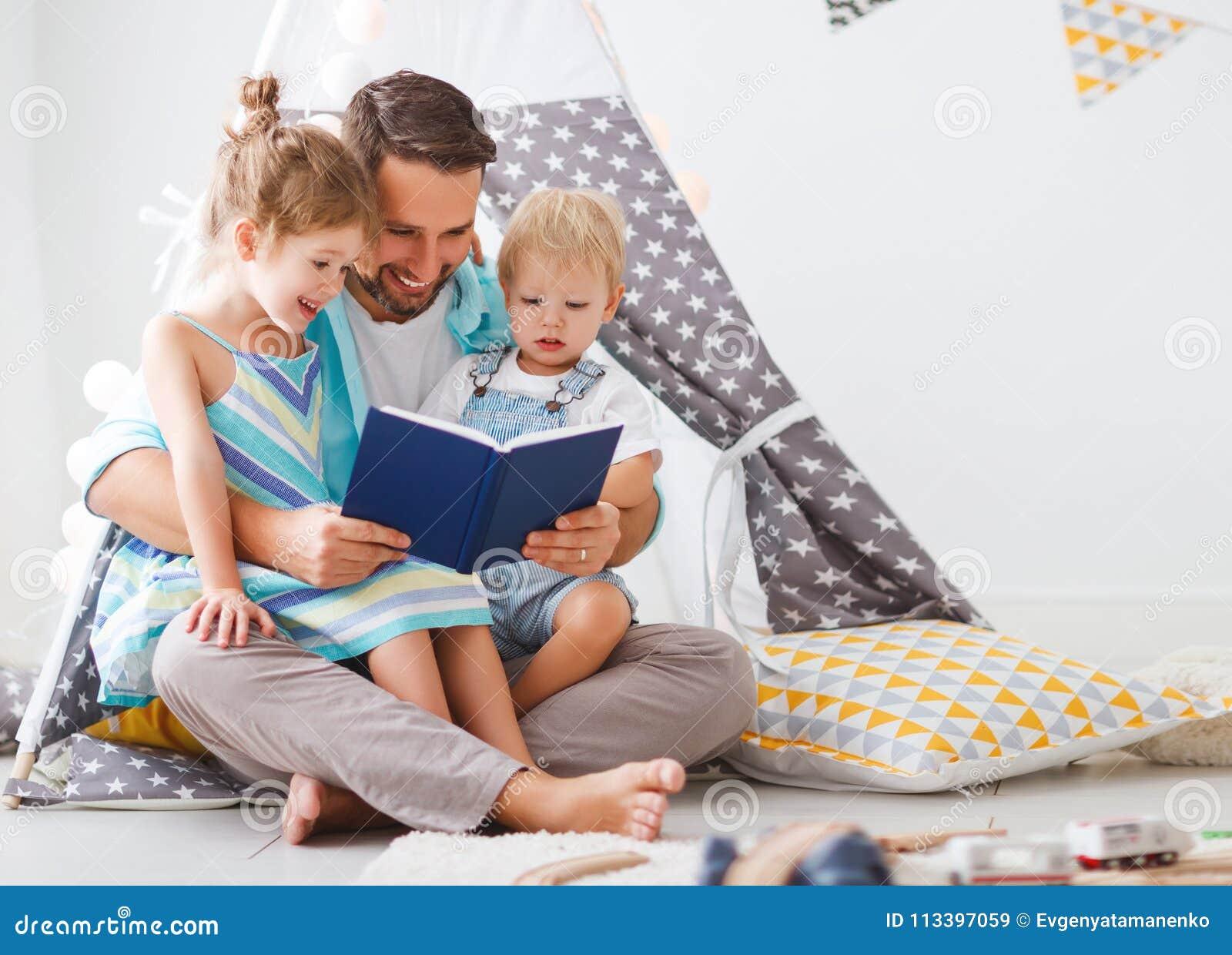 Pai da família que lê ao livro de crianças na barraca em casa