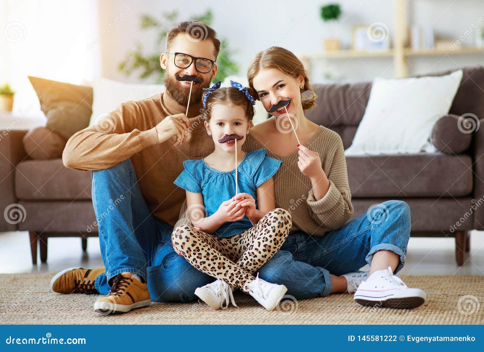 Pai da m?e da fam?lia e filha engra?ados felizes da crian?a com o bigode na vara