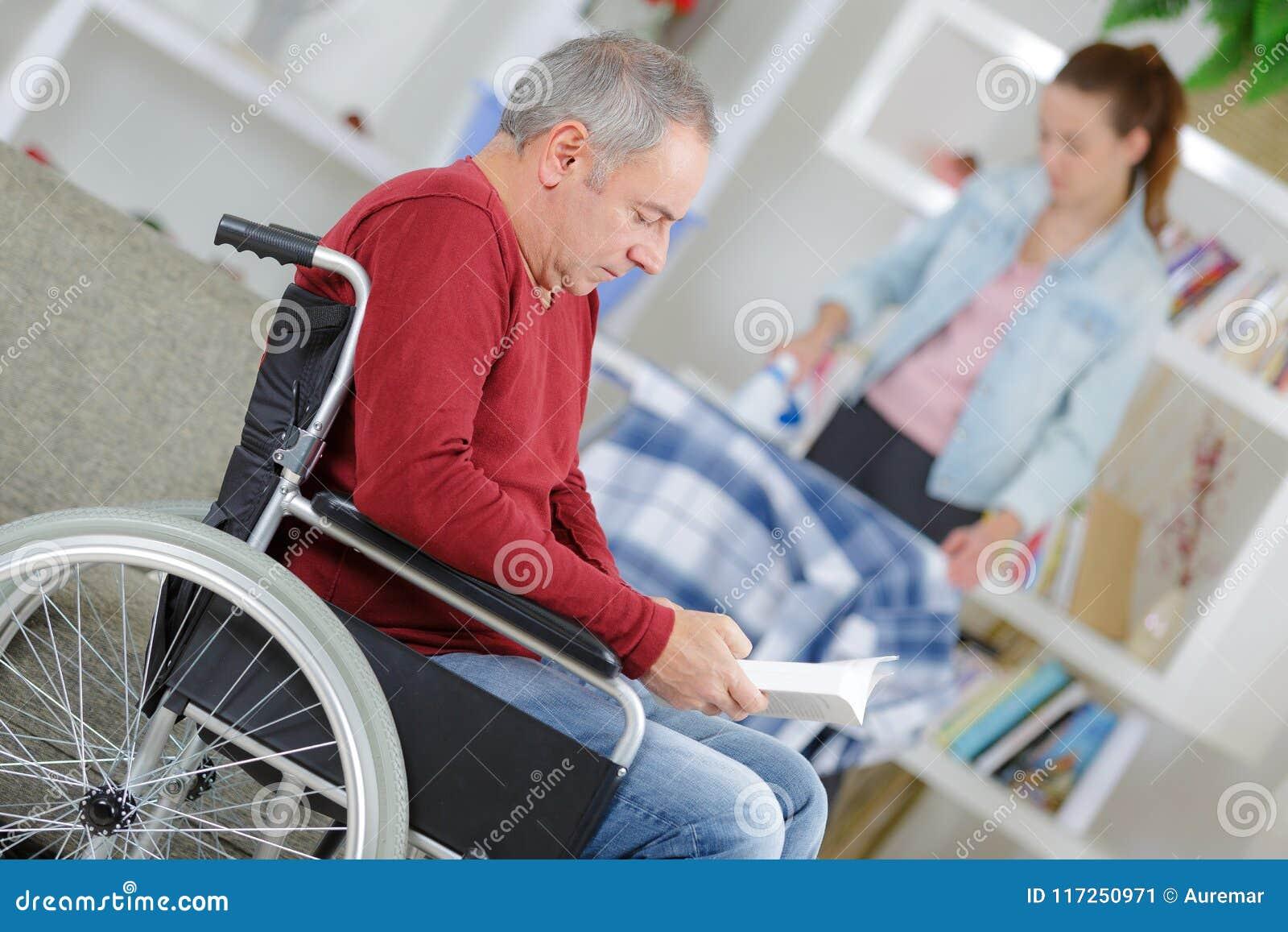 Pai de ajuda da filha na cadeira de rodas em casa