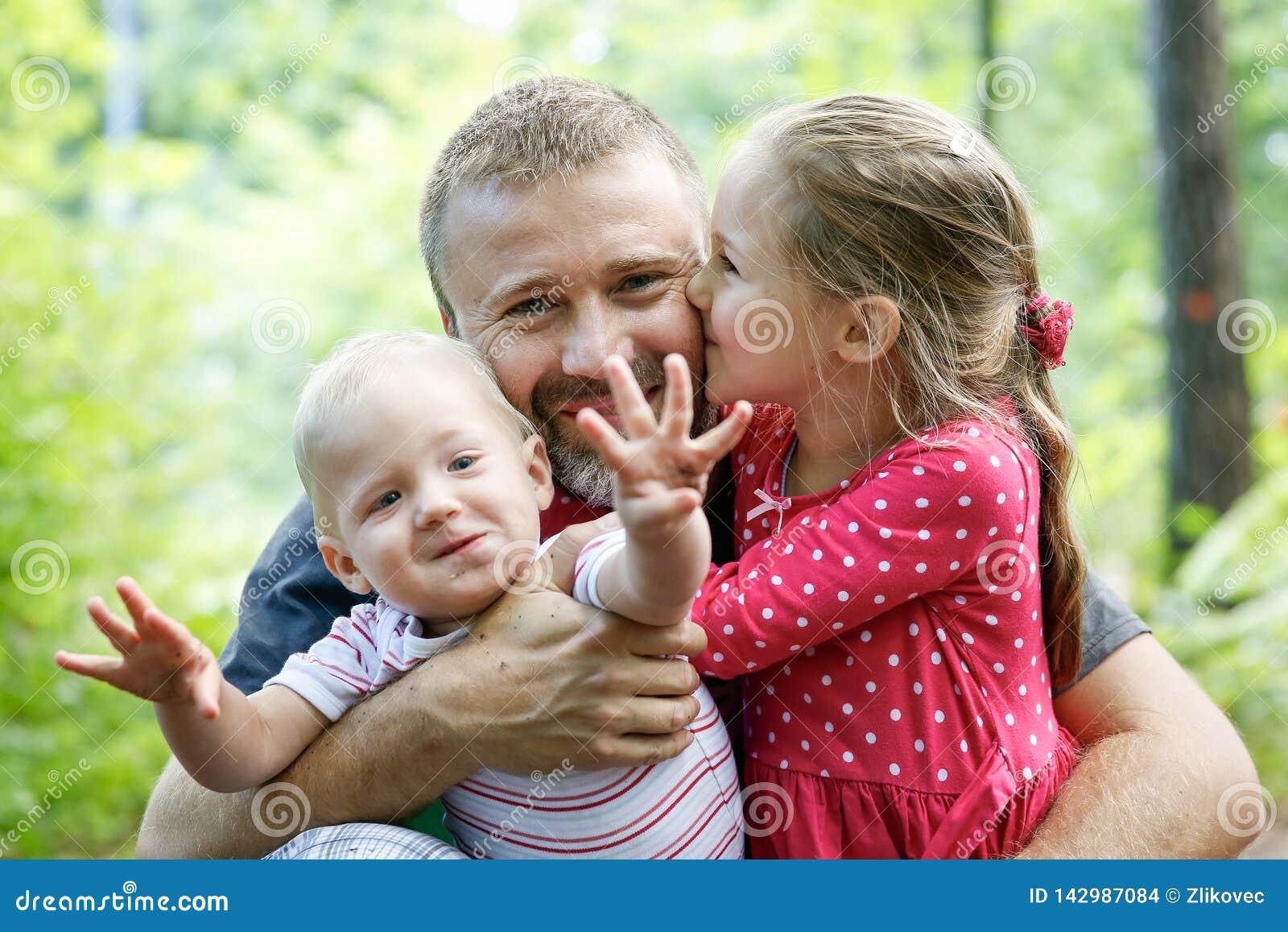 Pai devotado que abraça seus filho e filha, apreciando o exterior