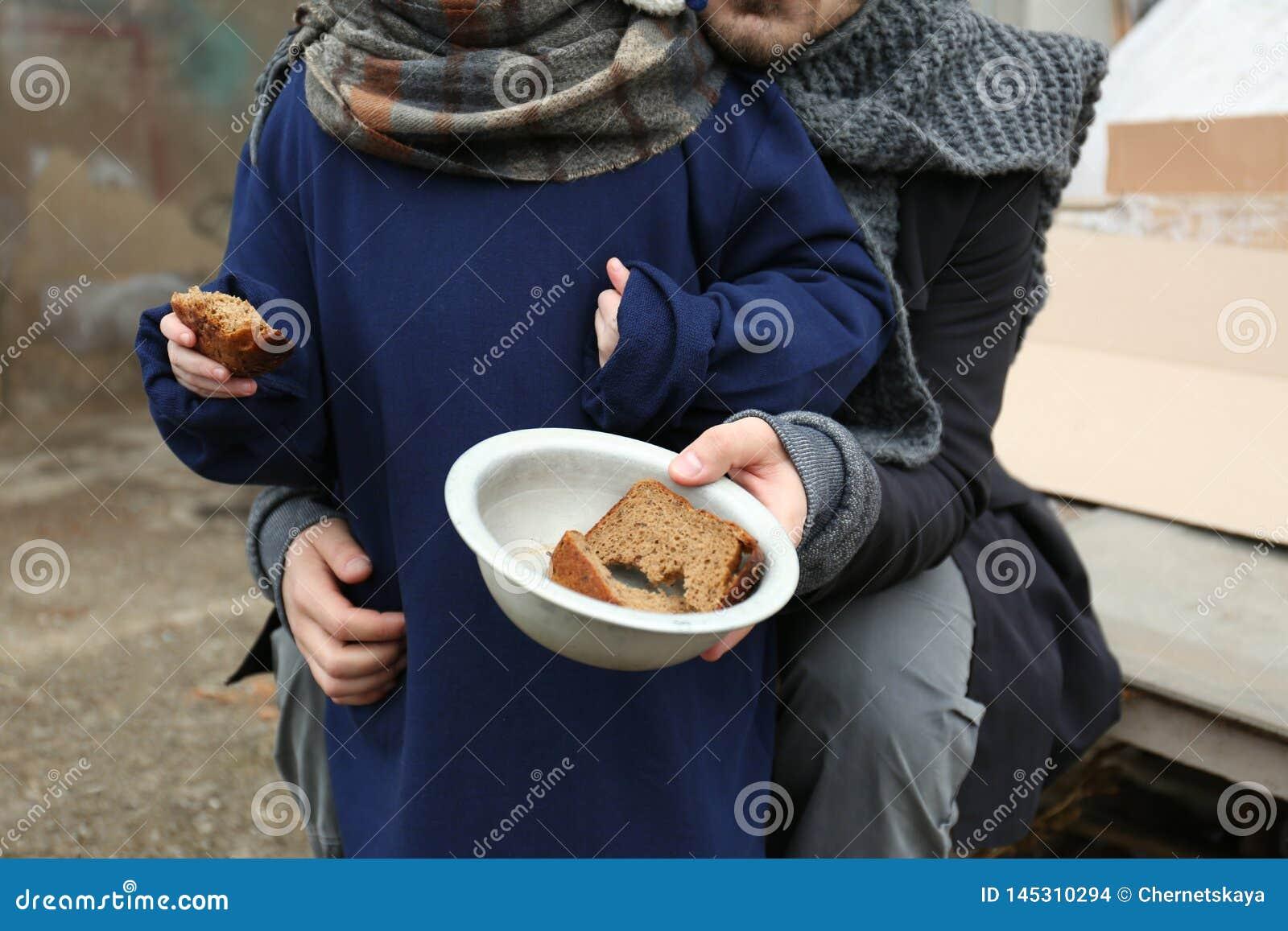 Pai e criança pobres com pão na descarga