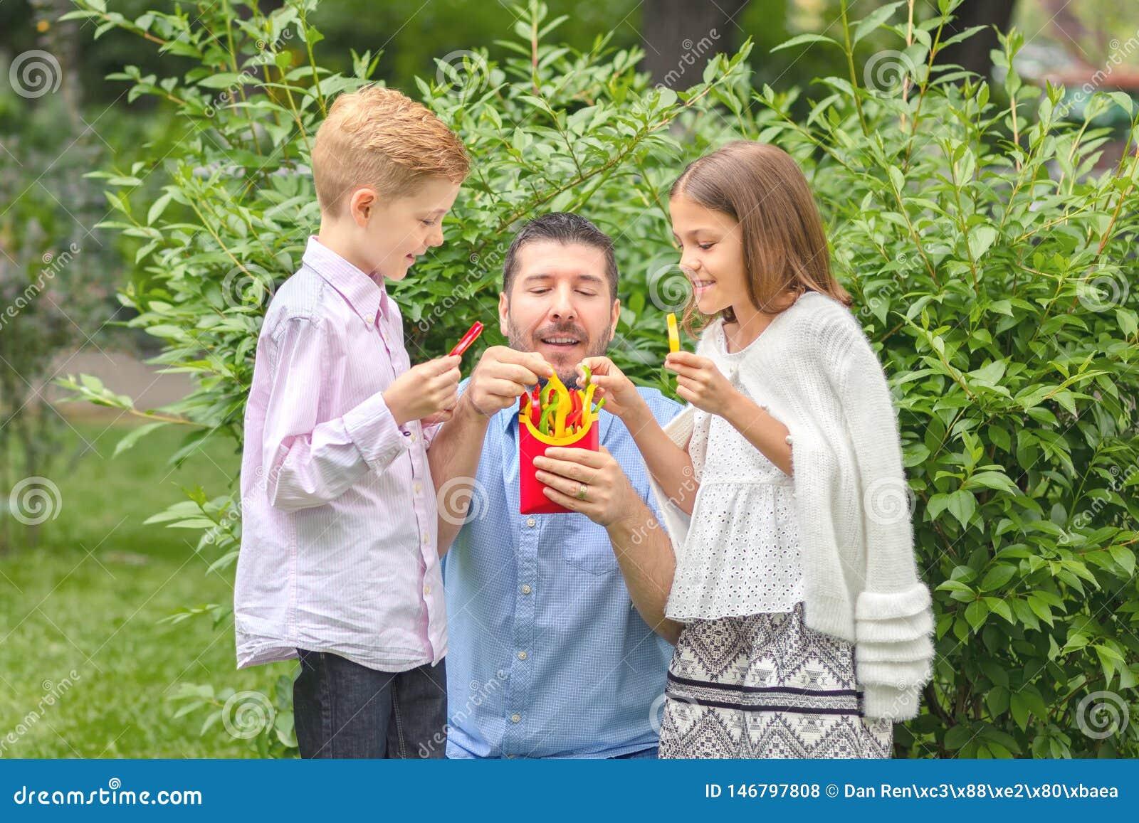 """Pai e crianças de sorriso que comem legumes frescos paizinho feliz no †da natureza """"que mantém pimentas coloridas cortadas no f"""