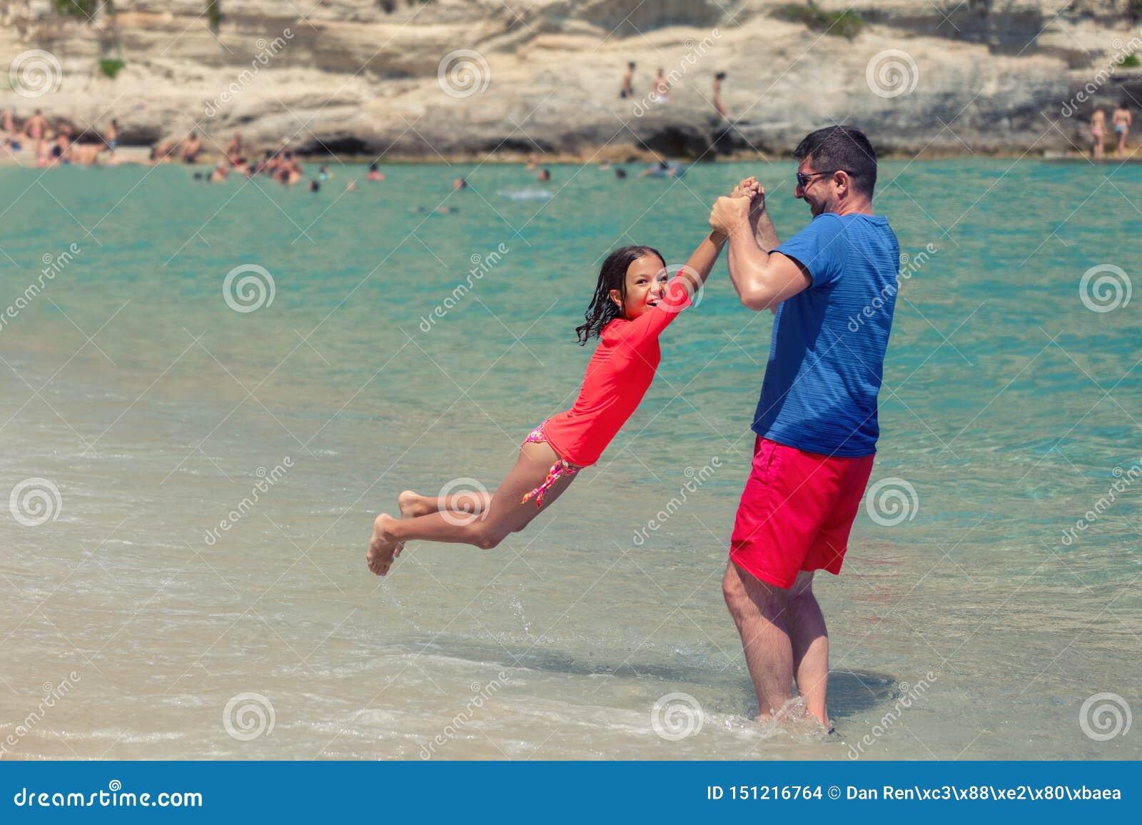Pai e filha de sorriso que jogam junto na praia, no paizinho feliz e na menina bonito jogando no beira-mar
