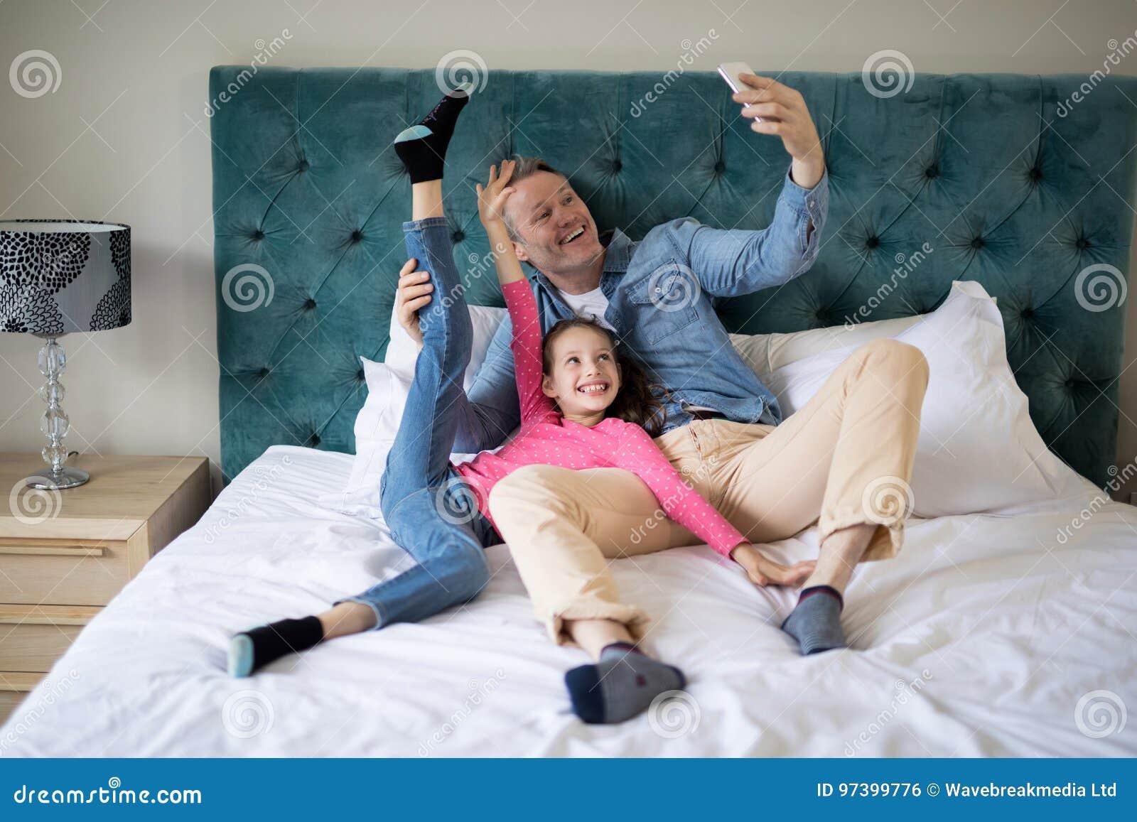 Pai e filha de sorriso que tomam o selfie com telefone celular na cama