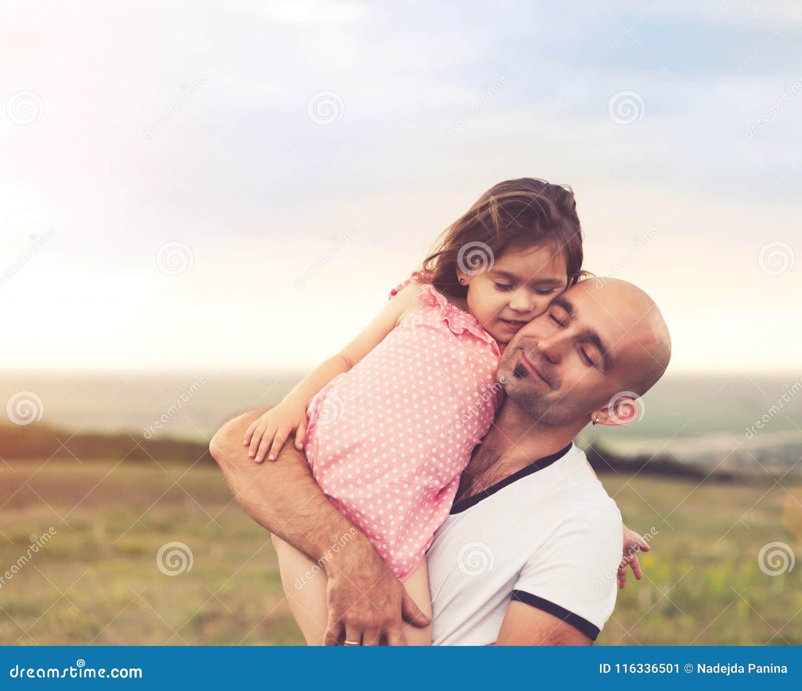 Pai e filha que abraçam no por do sol do verão