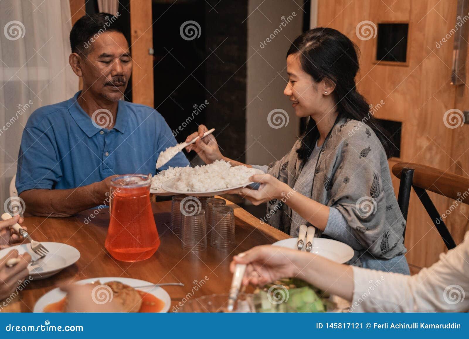 Pai e filha que comem o jantar junto