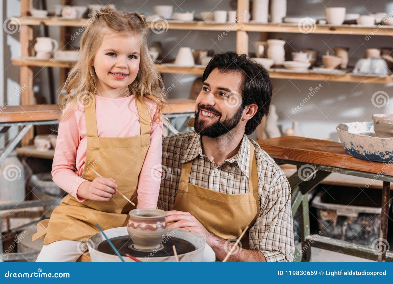 Pai e filha que pintam o professor cerâmico do potenciômetro