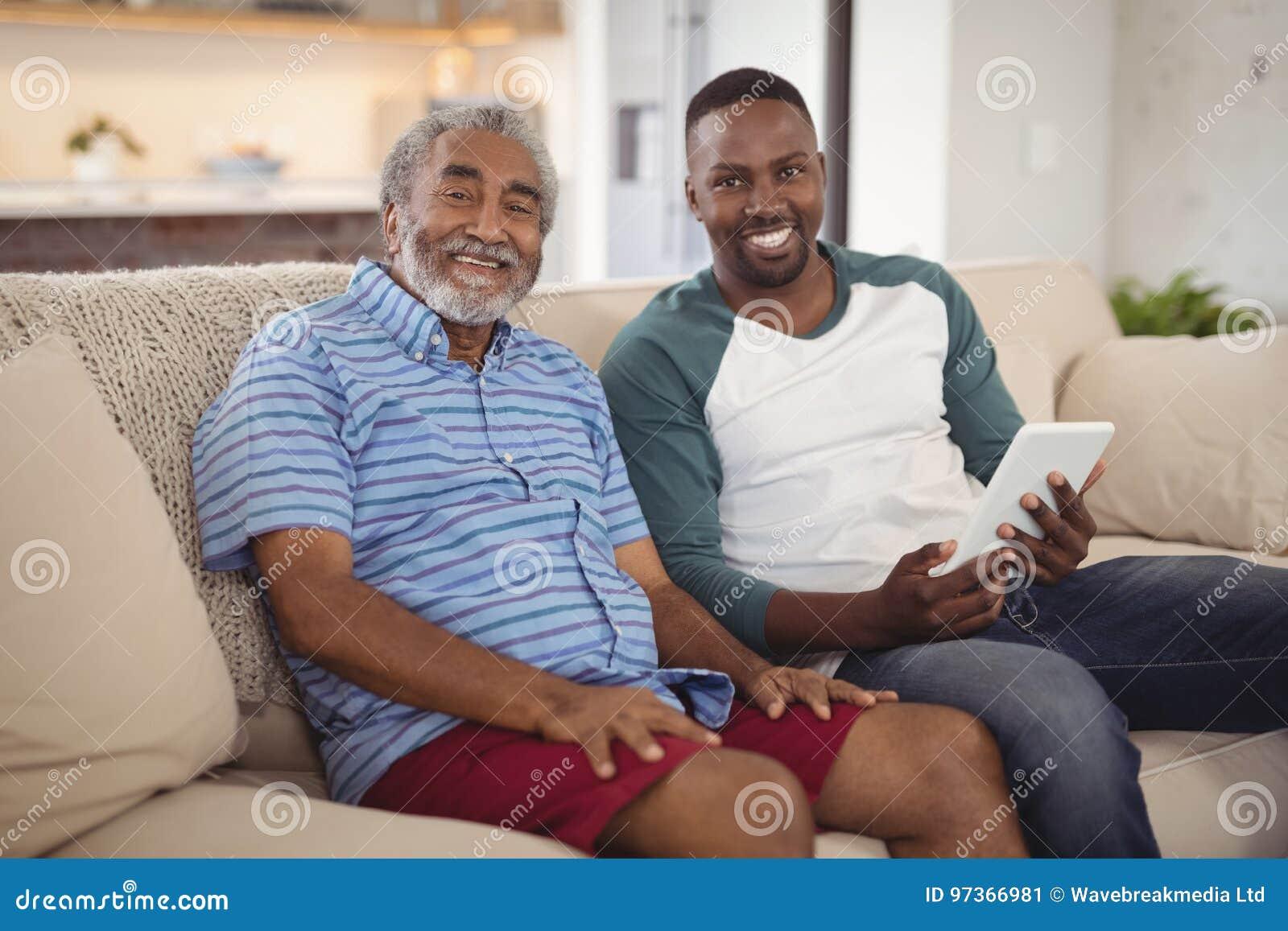 Pai e filho de sorriso que sentam-se no sofá com a tabuleta digital na sala de visitas