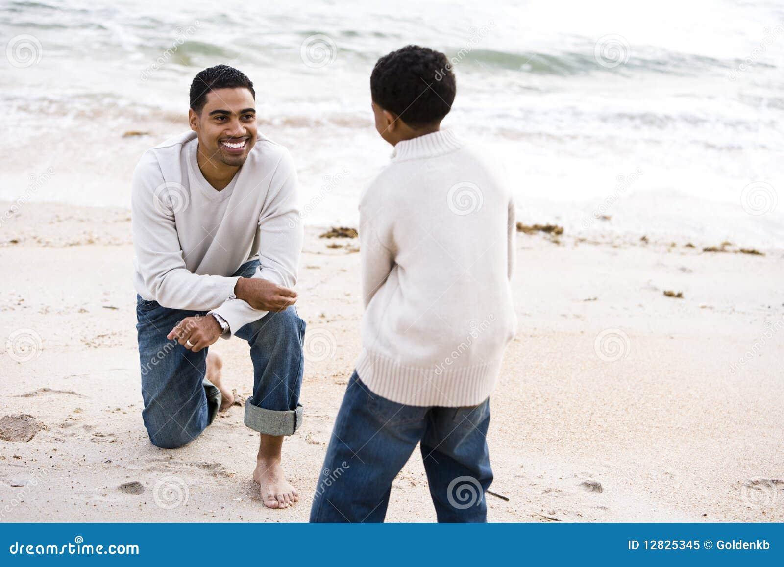 Pai e filho do African-American que jogam na praia