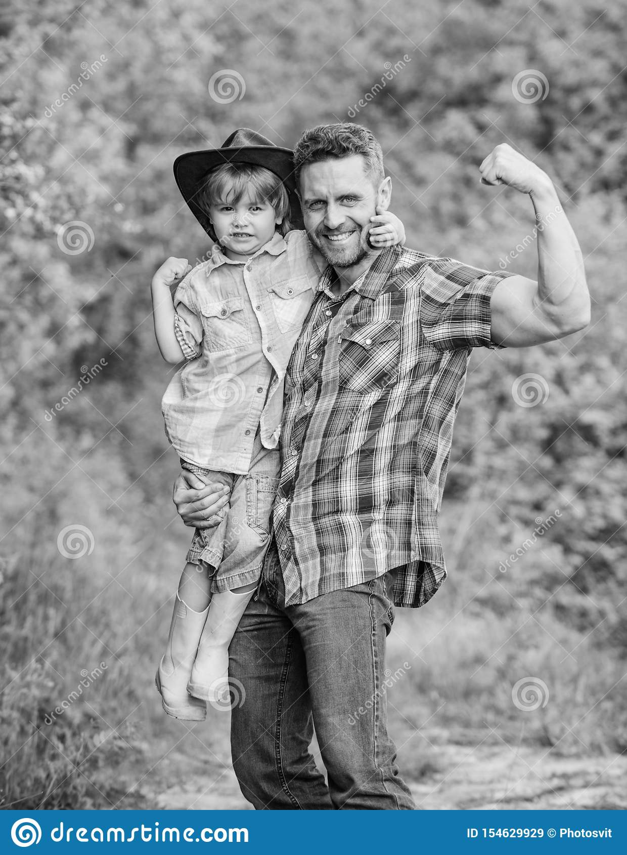 Pai e filho fortes no chap?u de vaqueiro no rancho crian?a nas botas de borracha Paizinho feliz do homem no ser humano e na natur