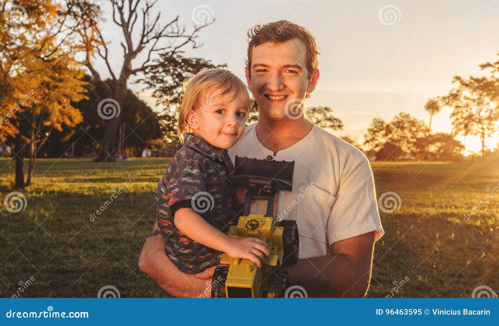 Pai e filho que riem junto em um por do sol bonito em um parque