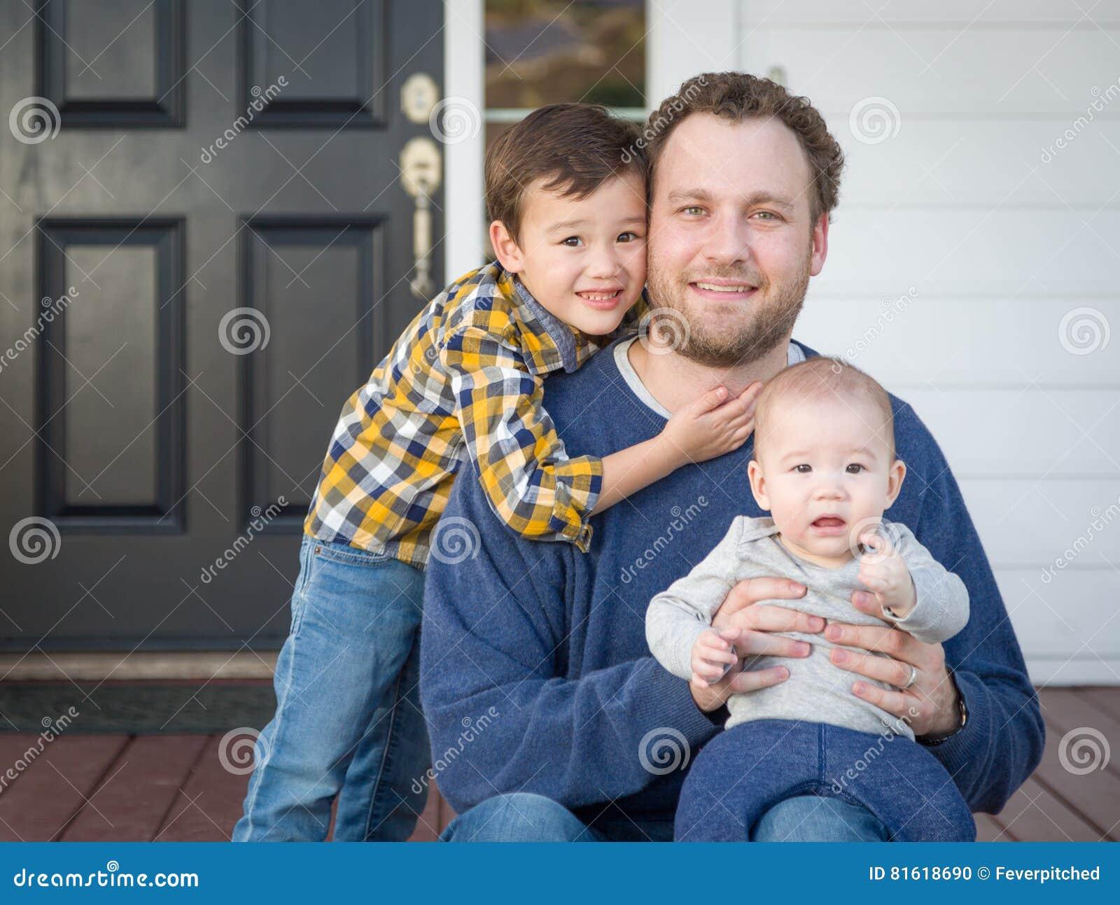 Pai e filhos da raça misturada em Front Porch