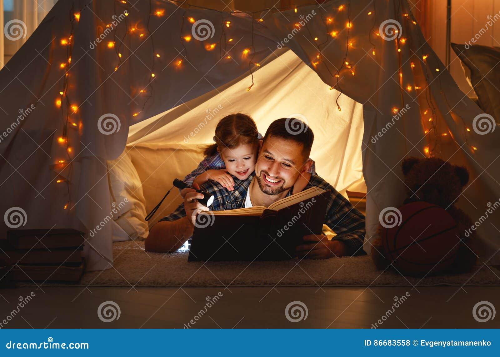 Pai feliz da família e filha da criança que lê um livro na barraca