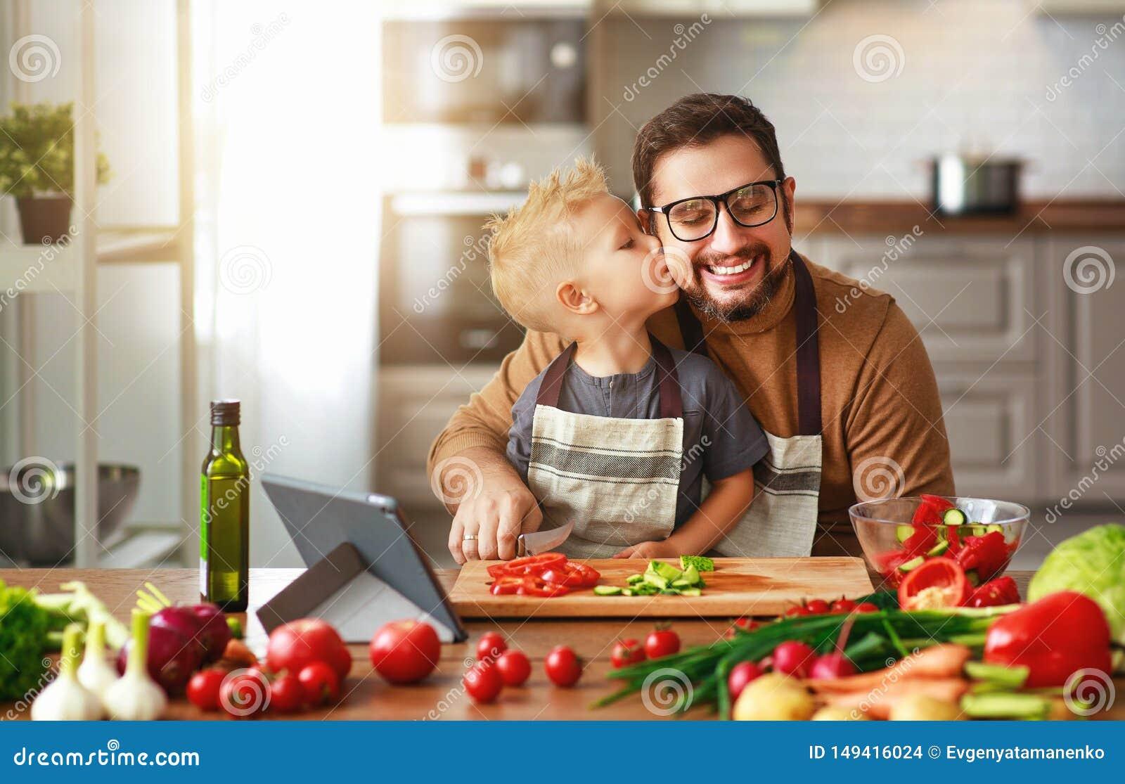 Pai feliz da fam?lia com o filho que prepara a salada vegetal