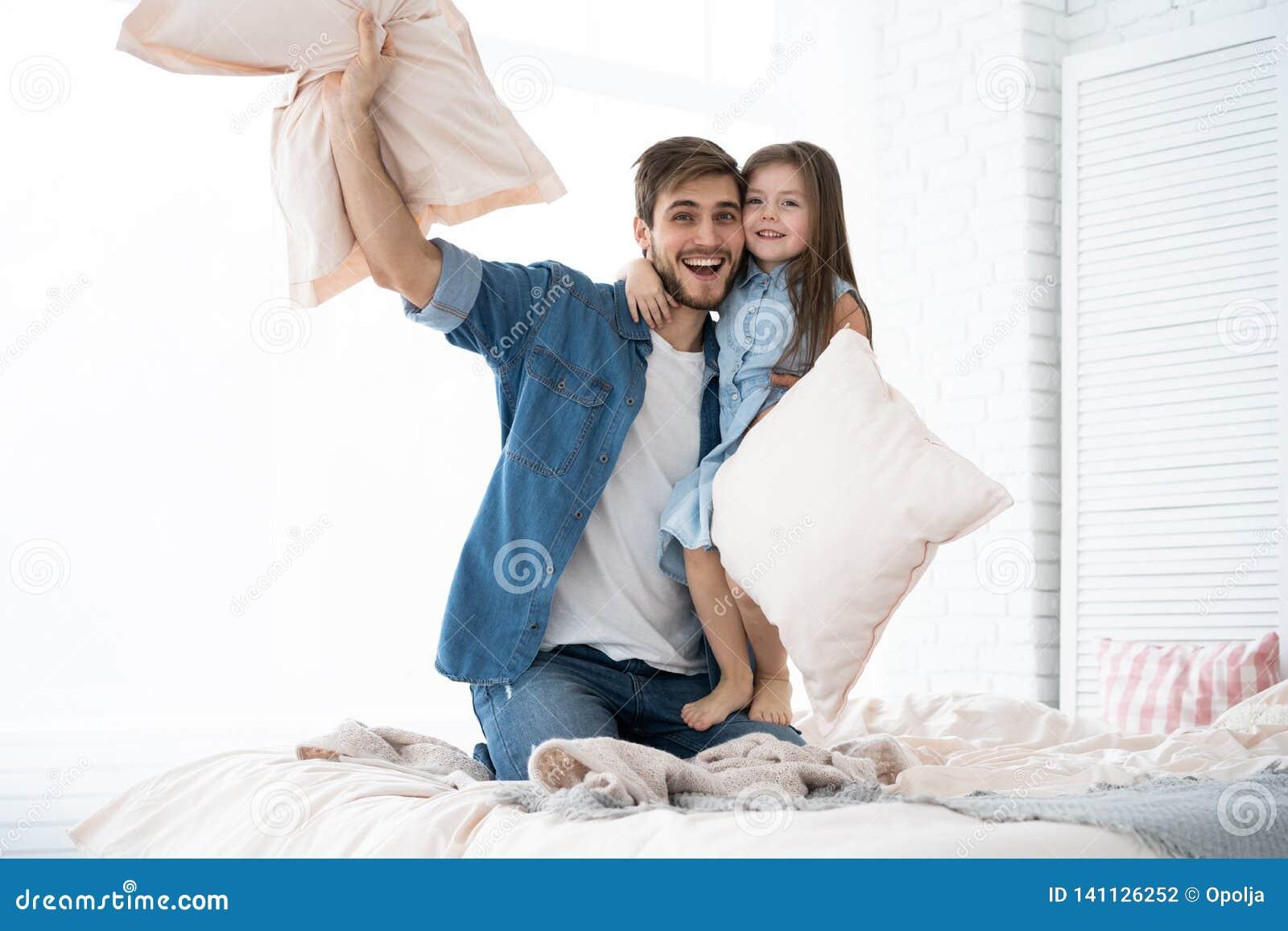 Pai feliz e filha que jogam a luta de descanso na cama na manhã