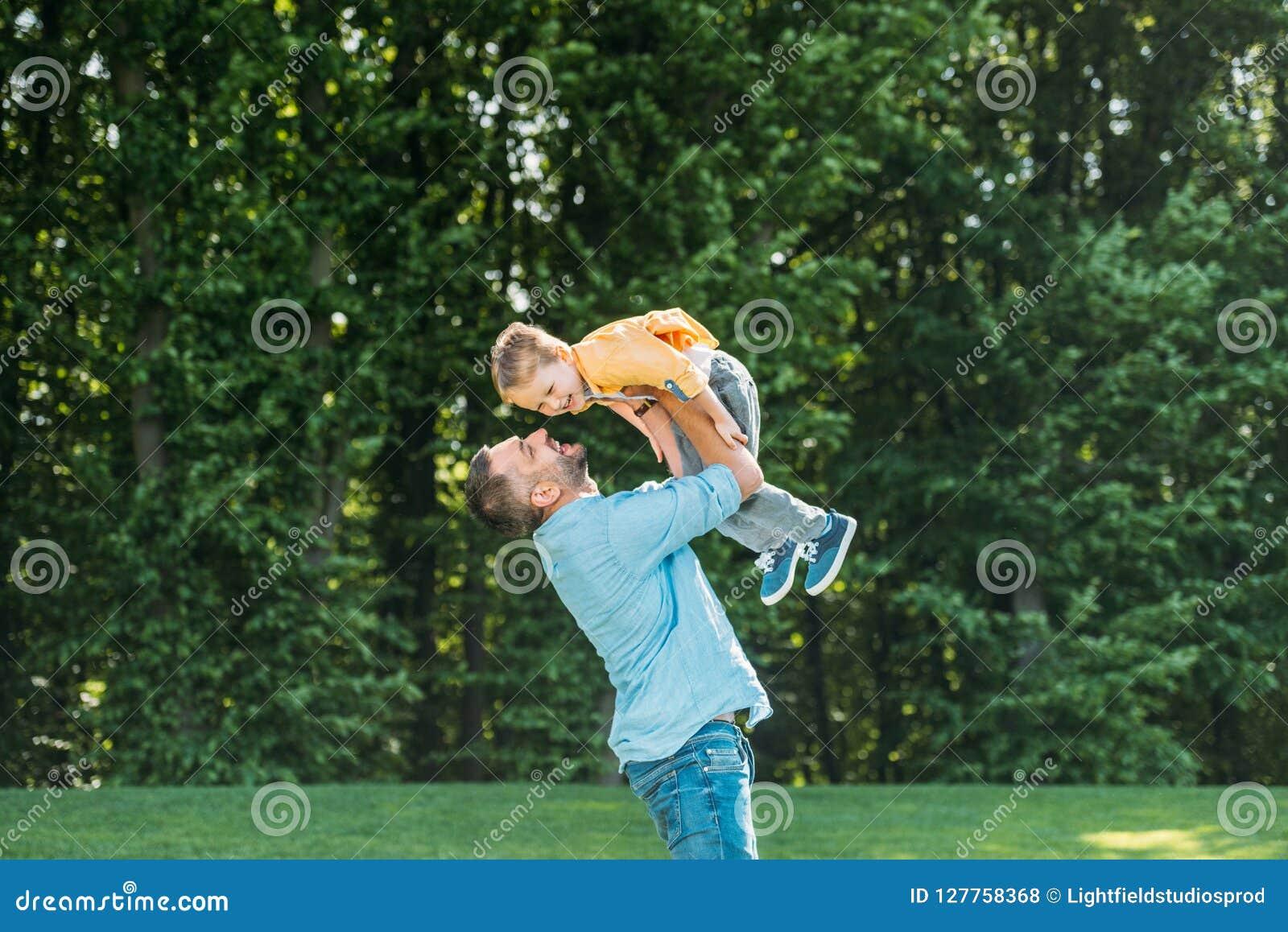Pai feliz que leva o filho pequeno de sorriso adorável
