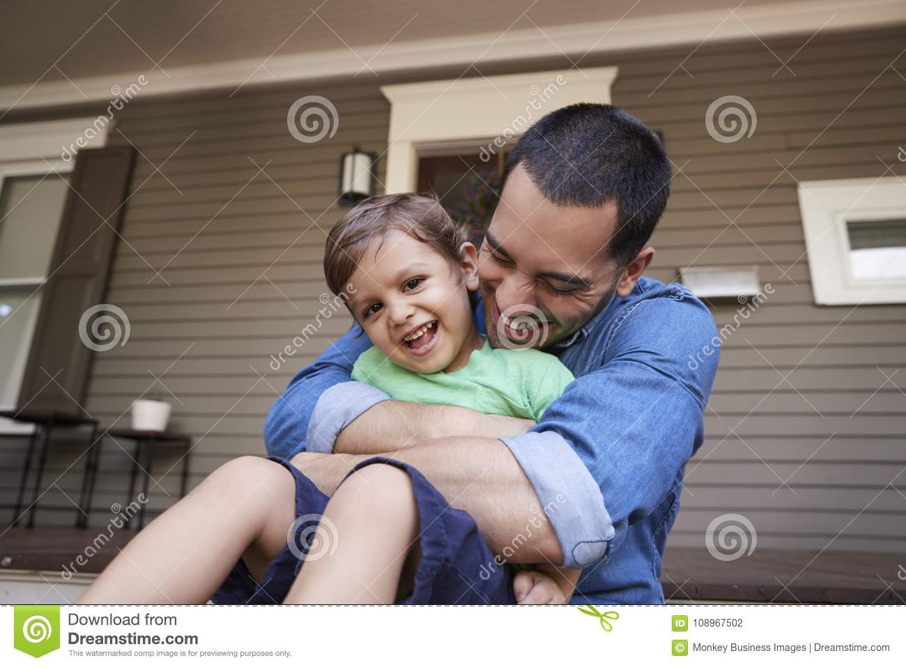 Pai Hugging Son As eles Sit On Porch Of House junto