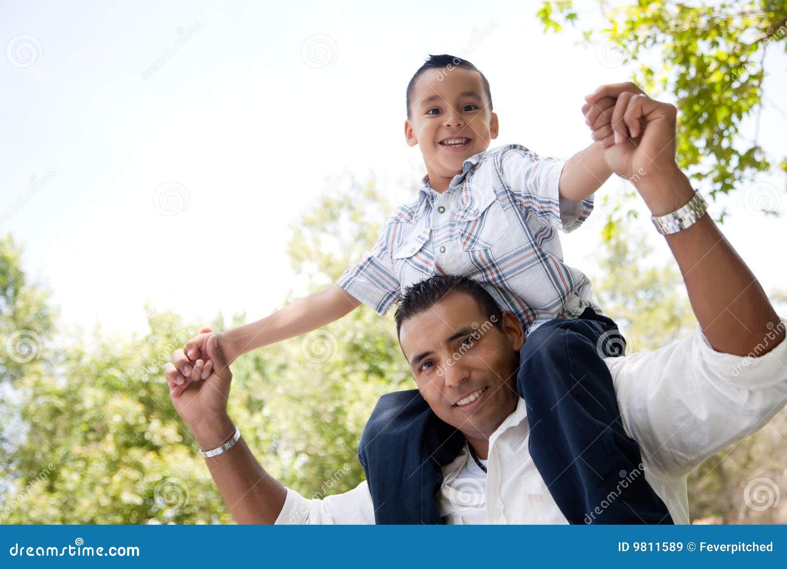 Pai latino-americano e filho que têm o divertimento no parque