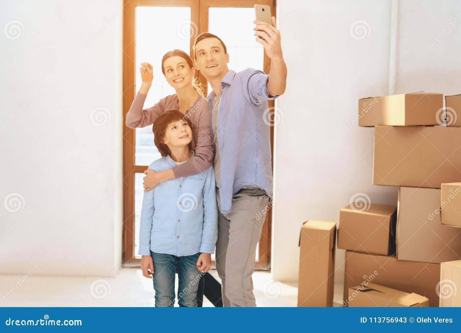 Pai, mãe e filho no apartamento novo com caixas de cartão A família está tomando o selfie no telefone