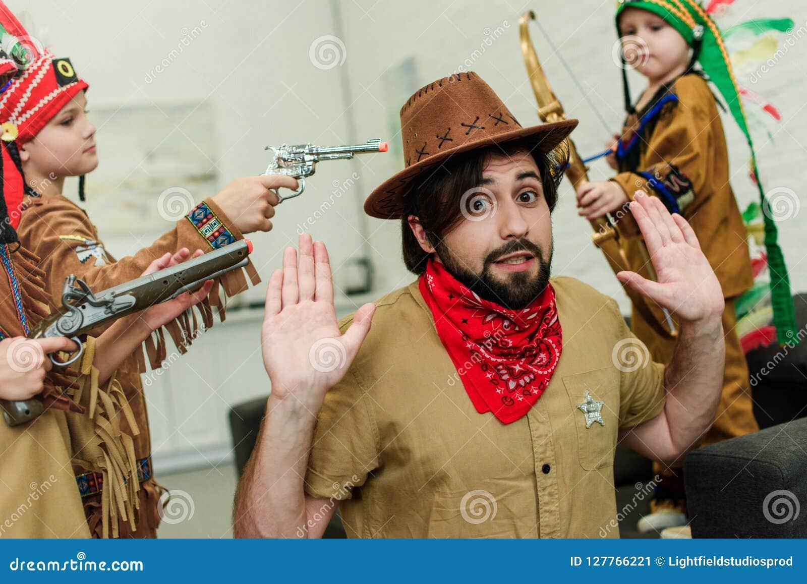 Pai no chapéu e no bandana e filhos pequenos em trajes nativos com os brinquedos que jogam junto