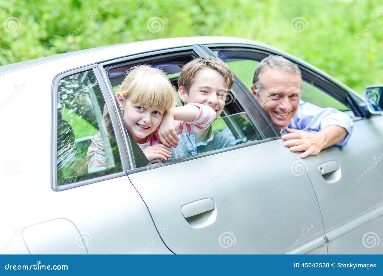 Pai que aprecia a movimentação do carro com suas crianças
