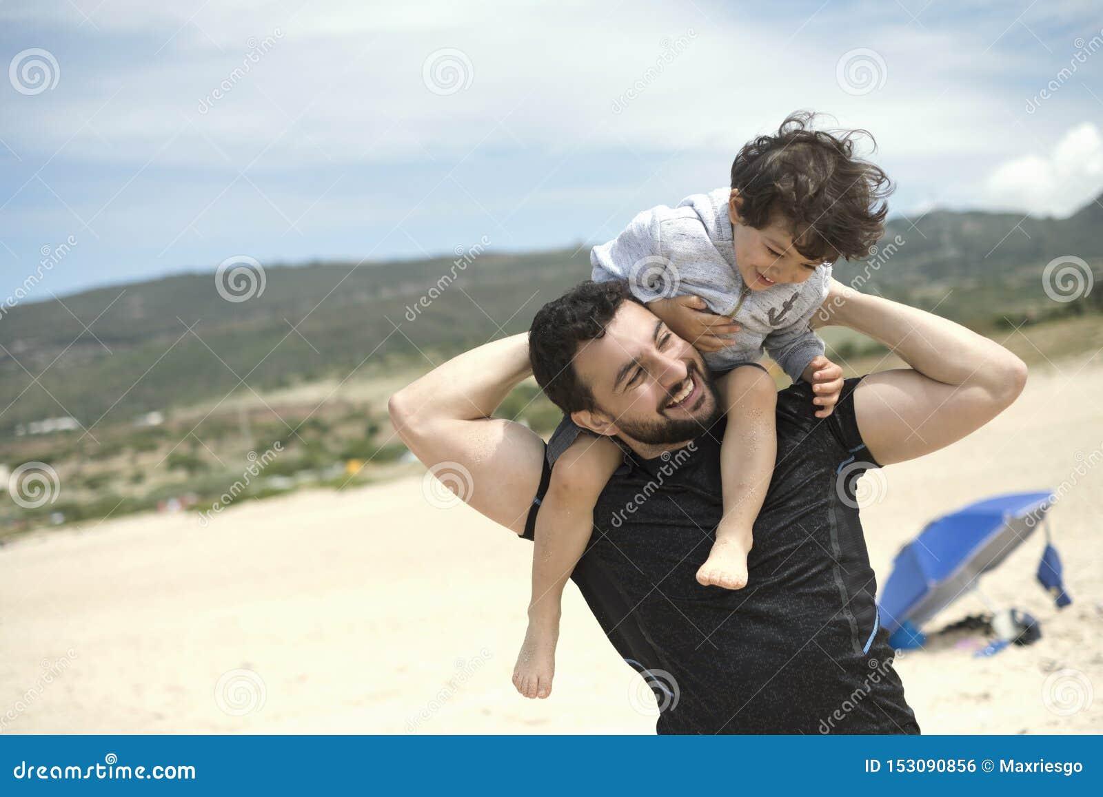 Pai que joga com o filho na praia de Bolonia