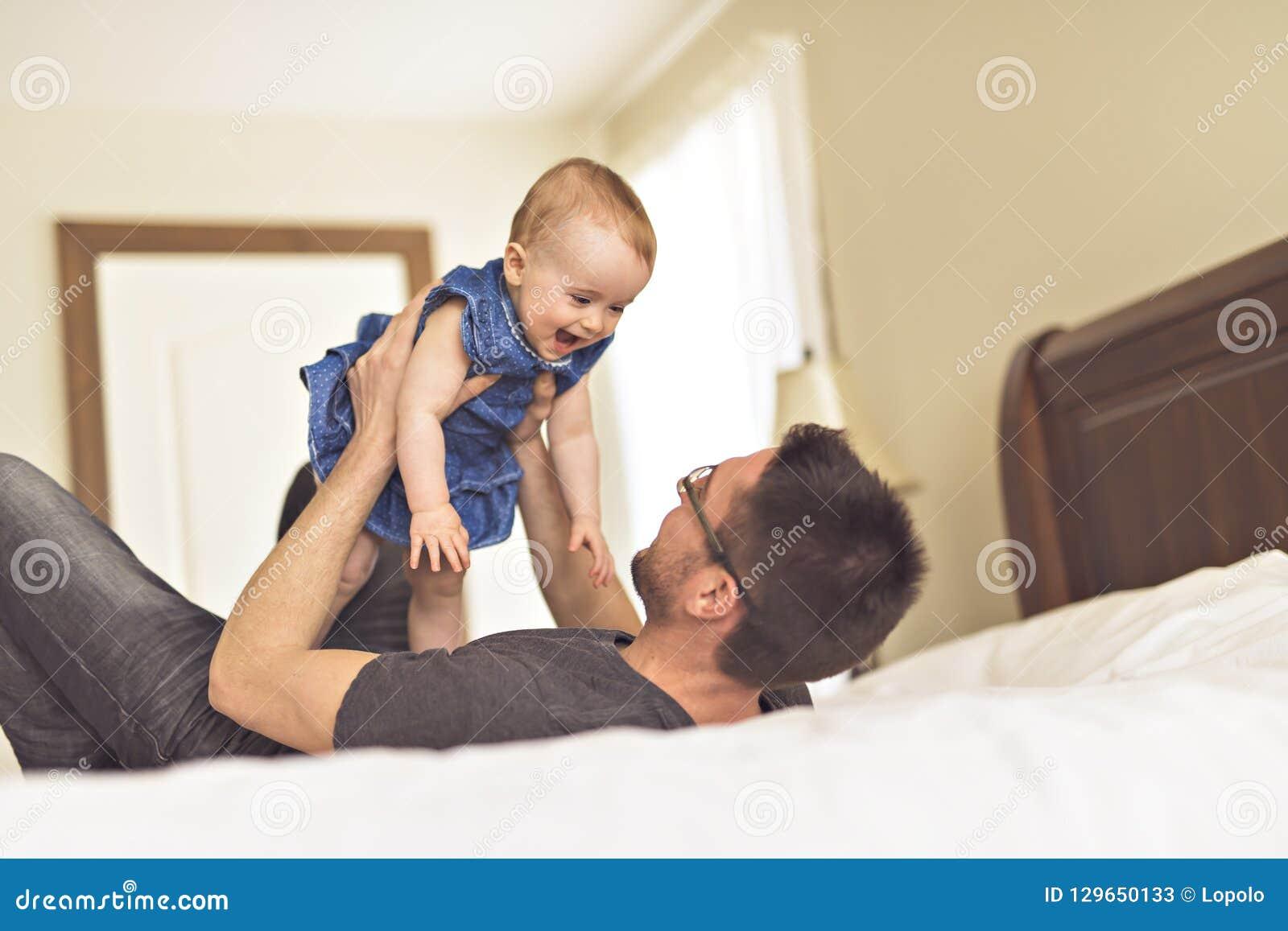 Pai que joga com seu bebê no quarto
