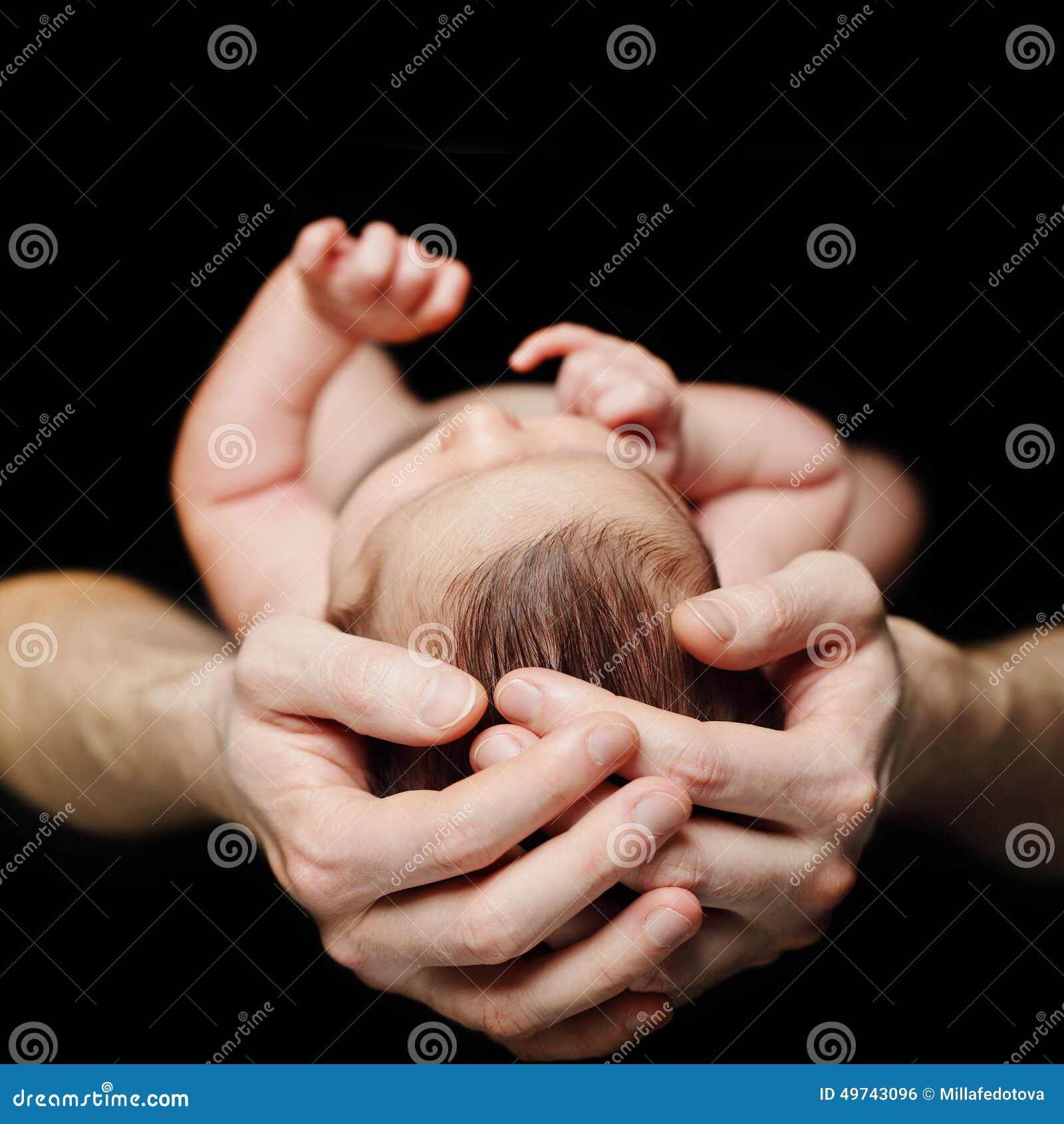 Pai que prende seu bebê recém-nascido