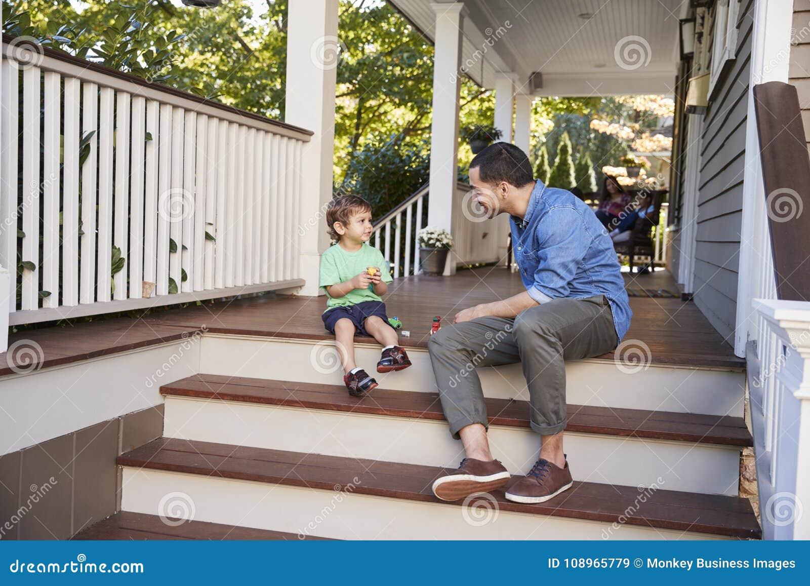Pai And Son Sit On Porch Of House que joga com brinquedos junto