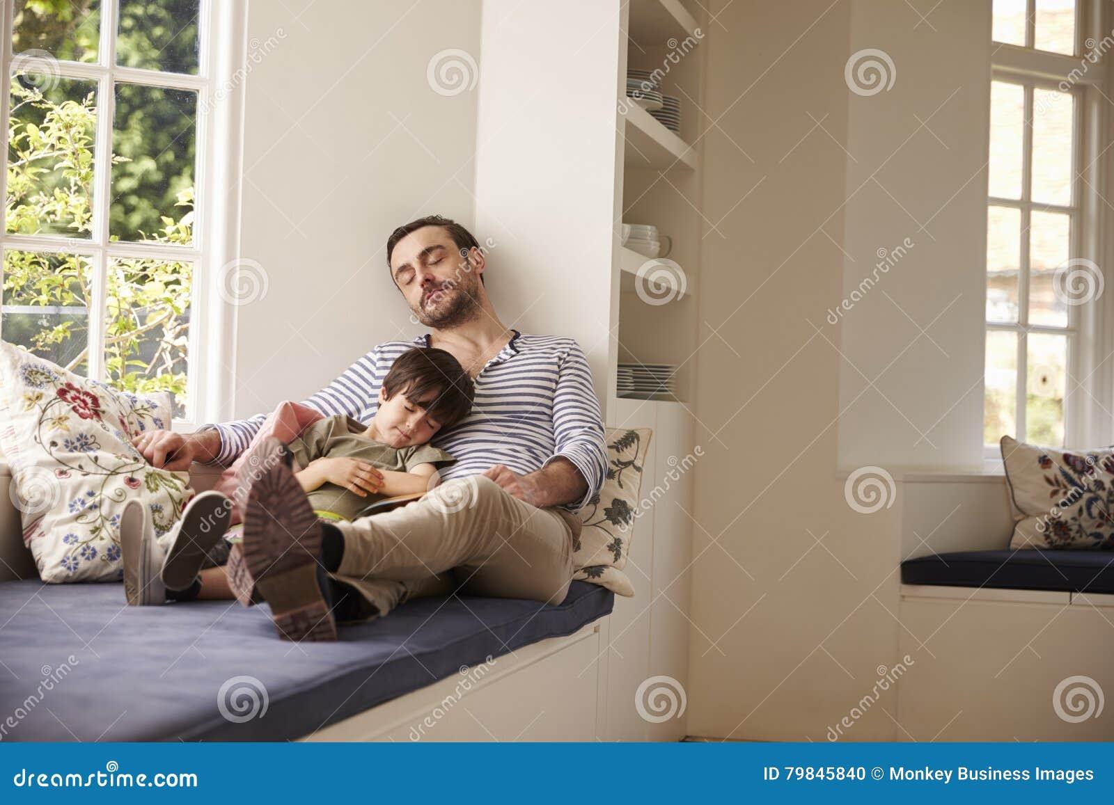 Pai And Son Sleeping na janela Seat em casa junto