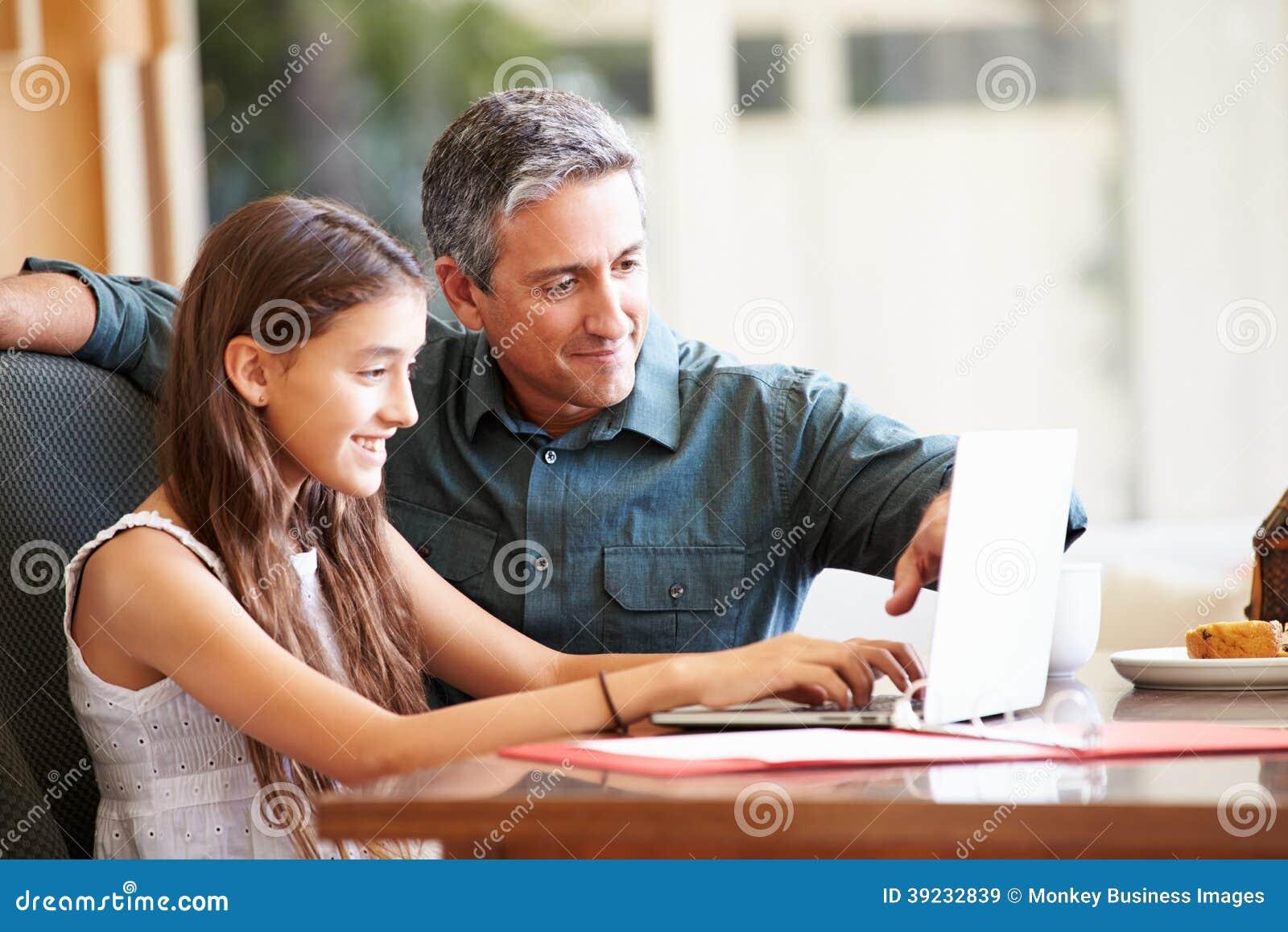 Pai And Teenage Daughter que olha o portátil junto
