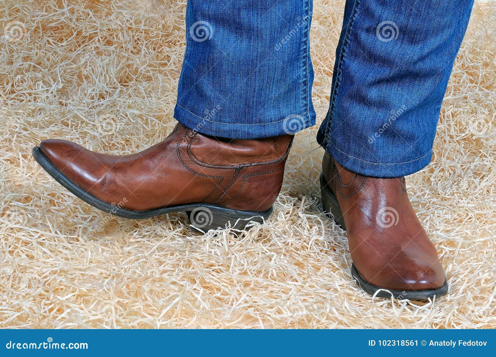 Paia Delle Gambe In Stivali E Jeans Di Cowboy Su Paglia