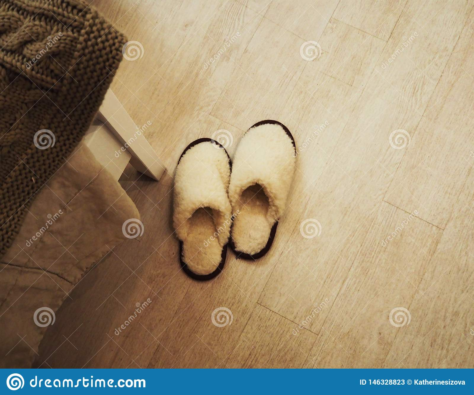 Paia delle pantofole accoglienti lanuginose sul pavimento in camera da letto