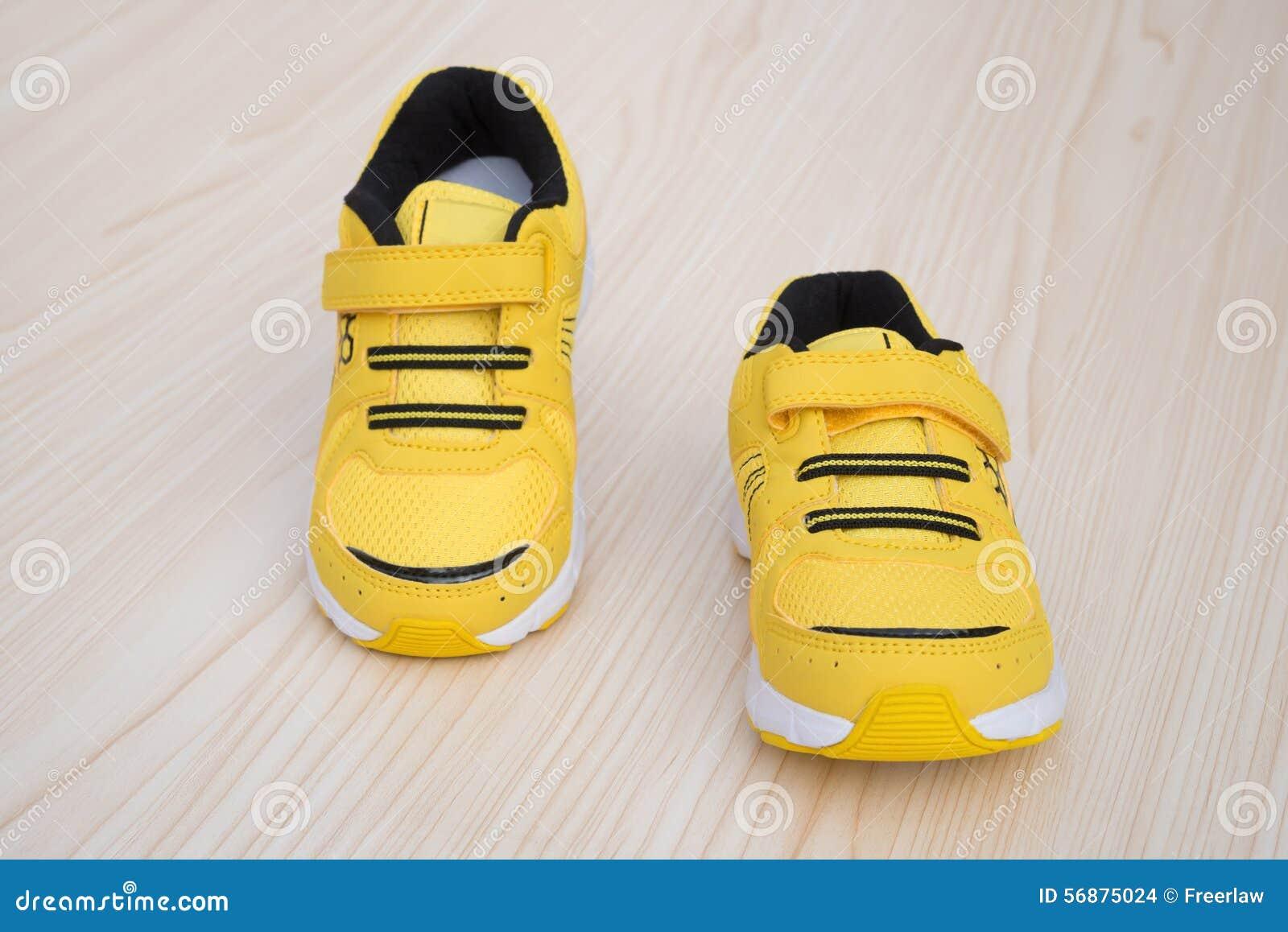 Paia delle scarpe sportive gialle per il bambino