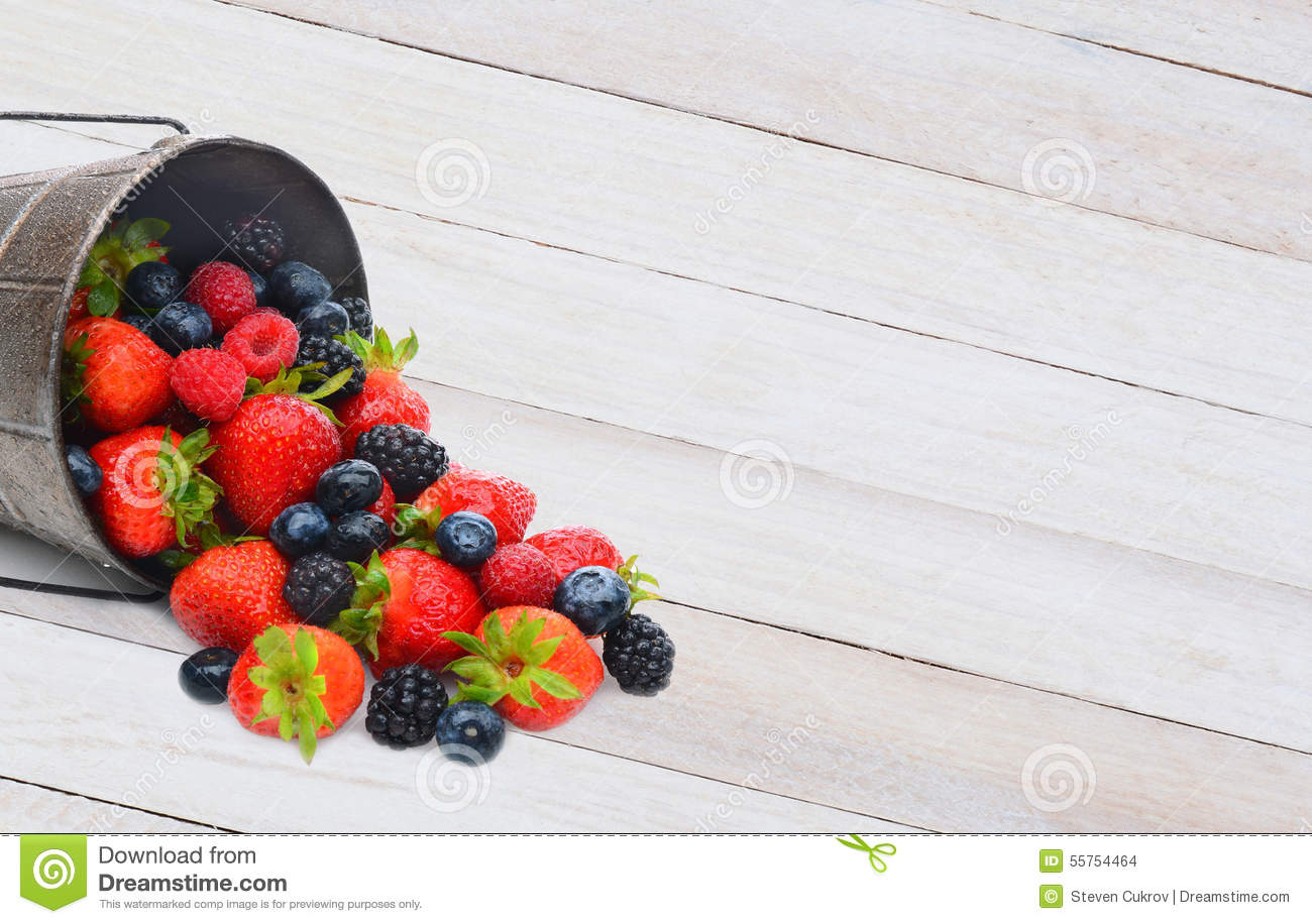 Pail with Berries Spilling on Wood Table