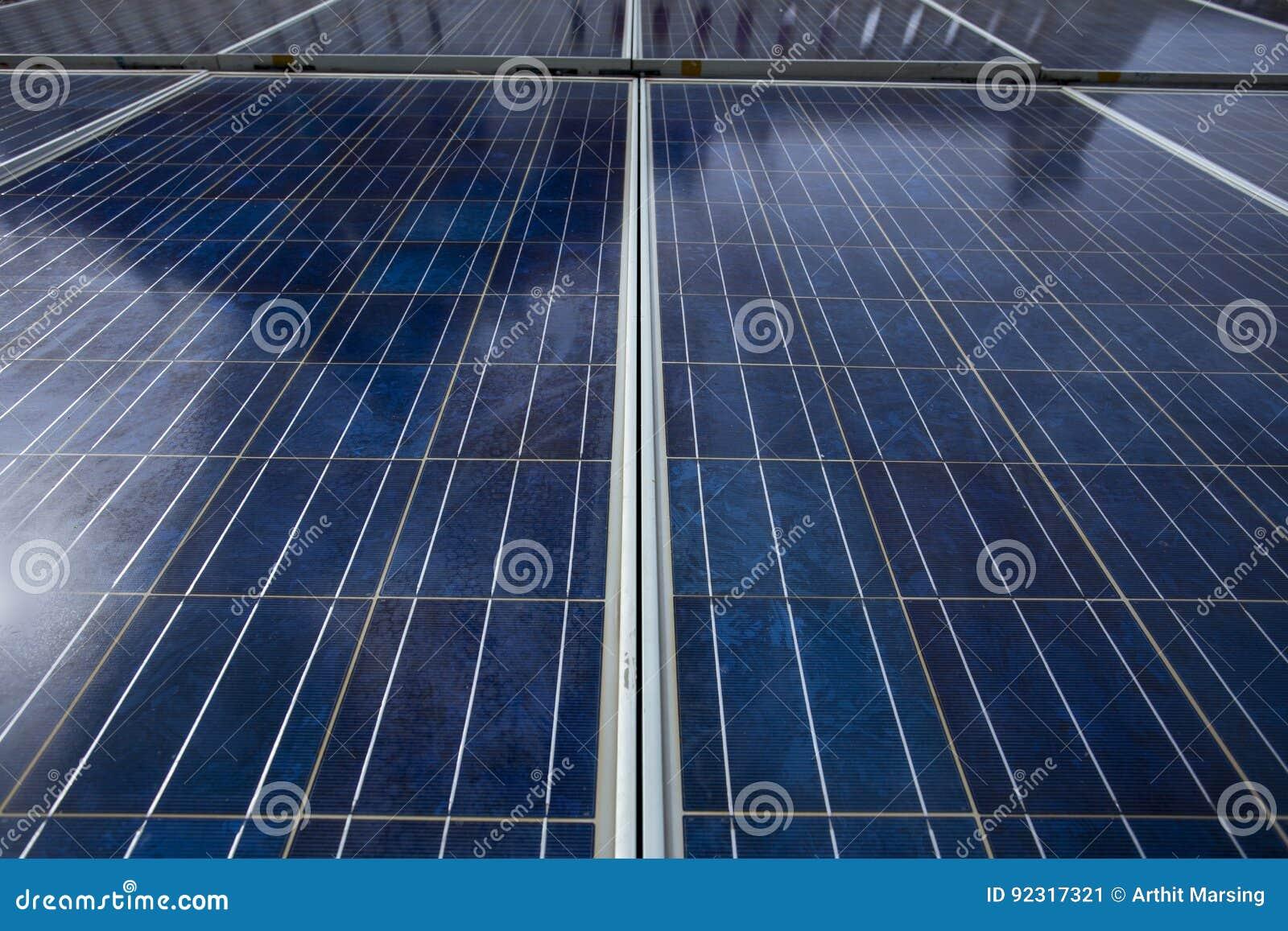 Painéis azuis da célula solar que mostrados suas linha e texturas de superfície de grade Os painéis estão contra a luz do sol no