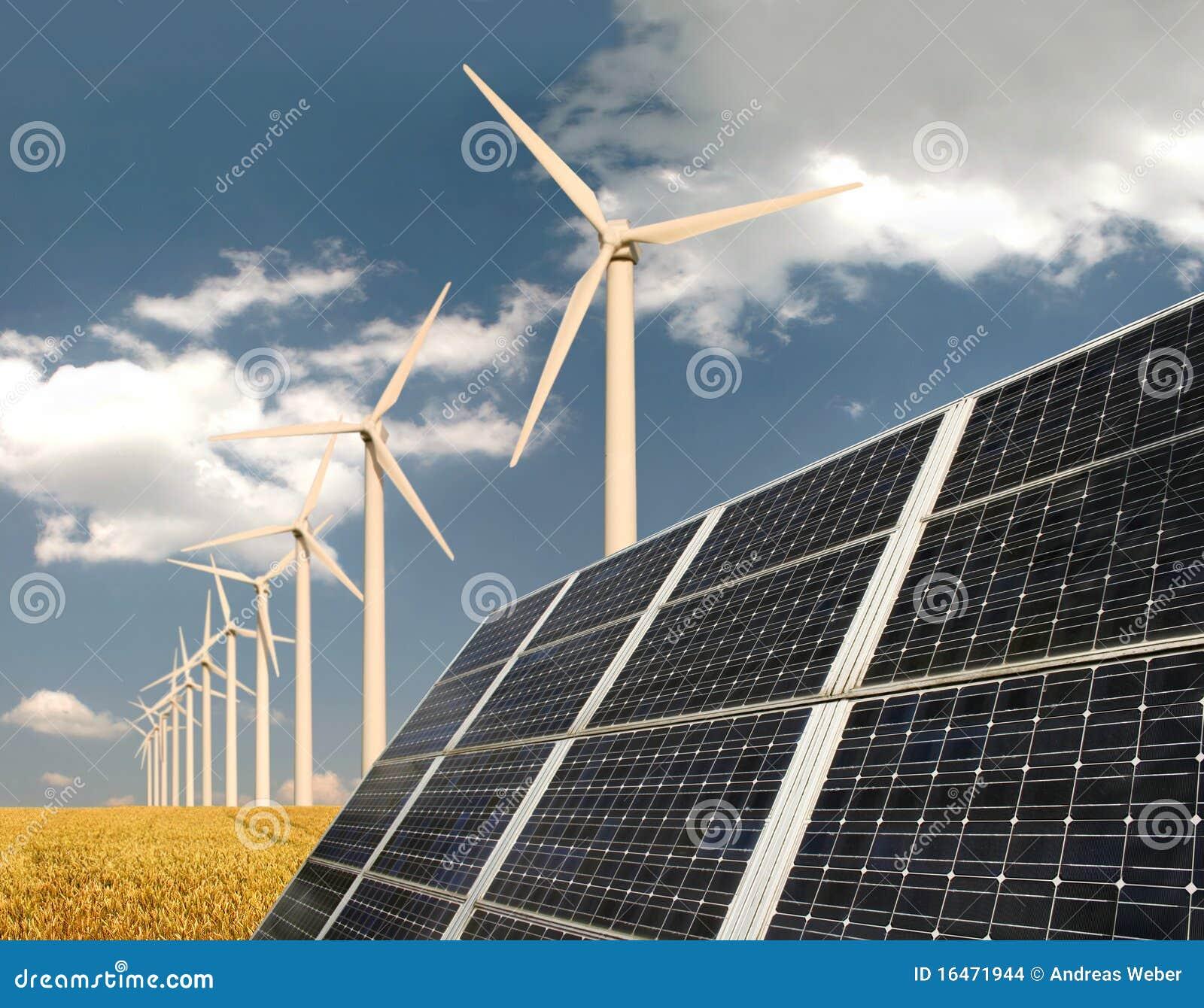 Painéis solares na frente das plantas de energia do vento